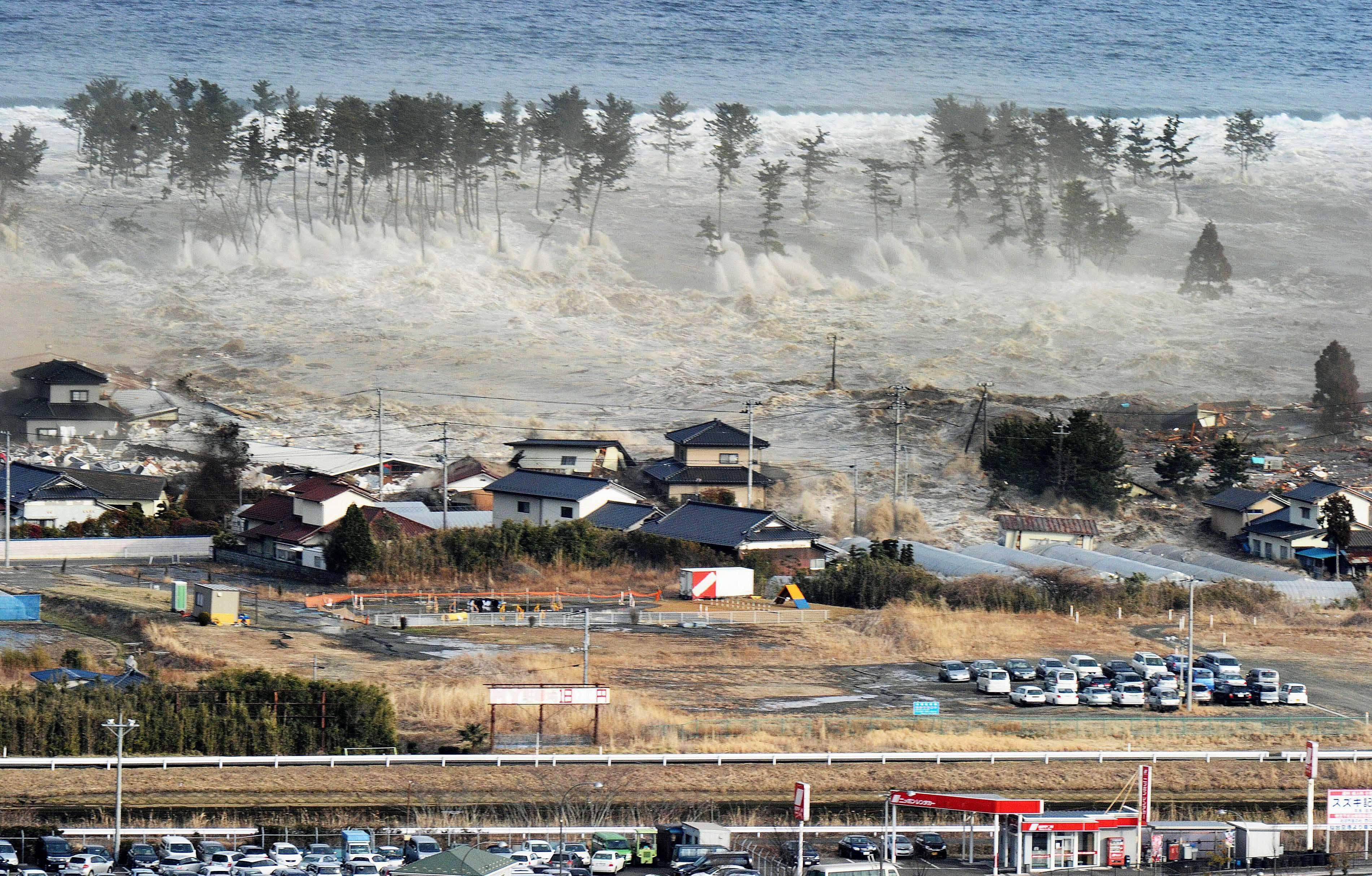 Waves of tsunami hit residences after a powerful earthquake in Natori, Miyagi prefecture (state), Japan, Friday.