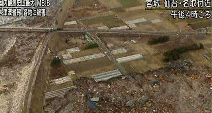 In this video image taken from Japan's NHK TV, houses, cars and debris half submerged is swept toward a highway by a tsunami in the Sendai city area, Miyagi Prefecture (state) Friday.