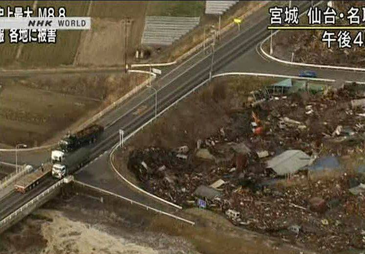 In this video image taken from Japan's NHK TV, houses, cars and debris half submerged is swept toward a highway by a tsunami in the Sendai city are.