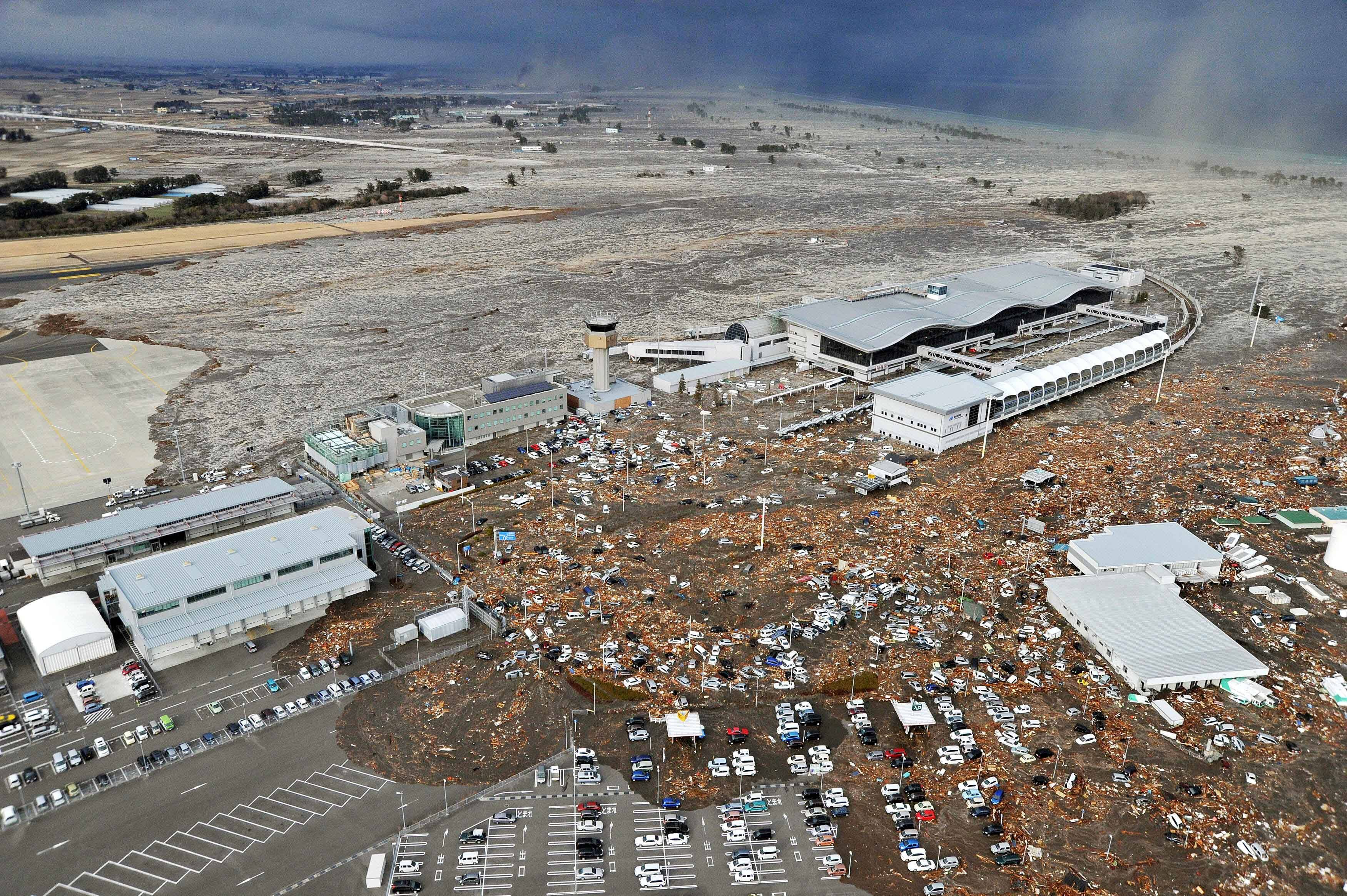 Tarmac, parking lot and surrounding area are covered with mud and debris carried by tsunami at Sendai Airport in Sendai, Miyagi Prefecture (state) after Japan was struck by a strong earthquake off its northeastern coast Friday.