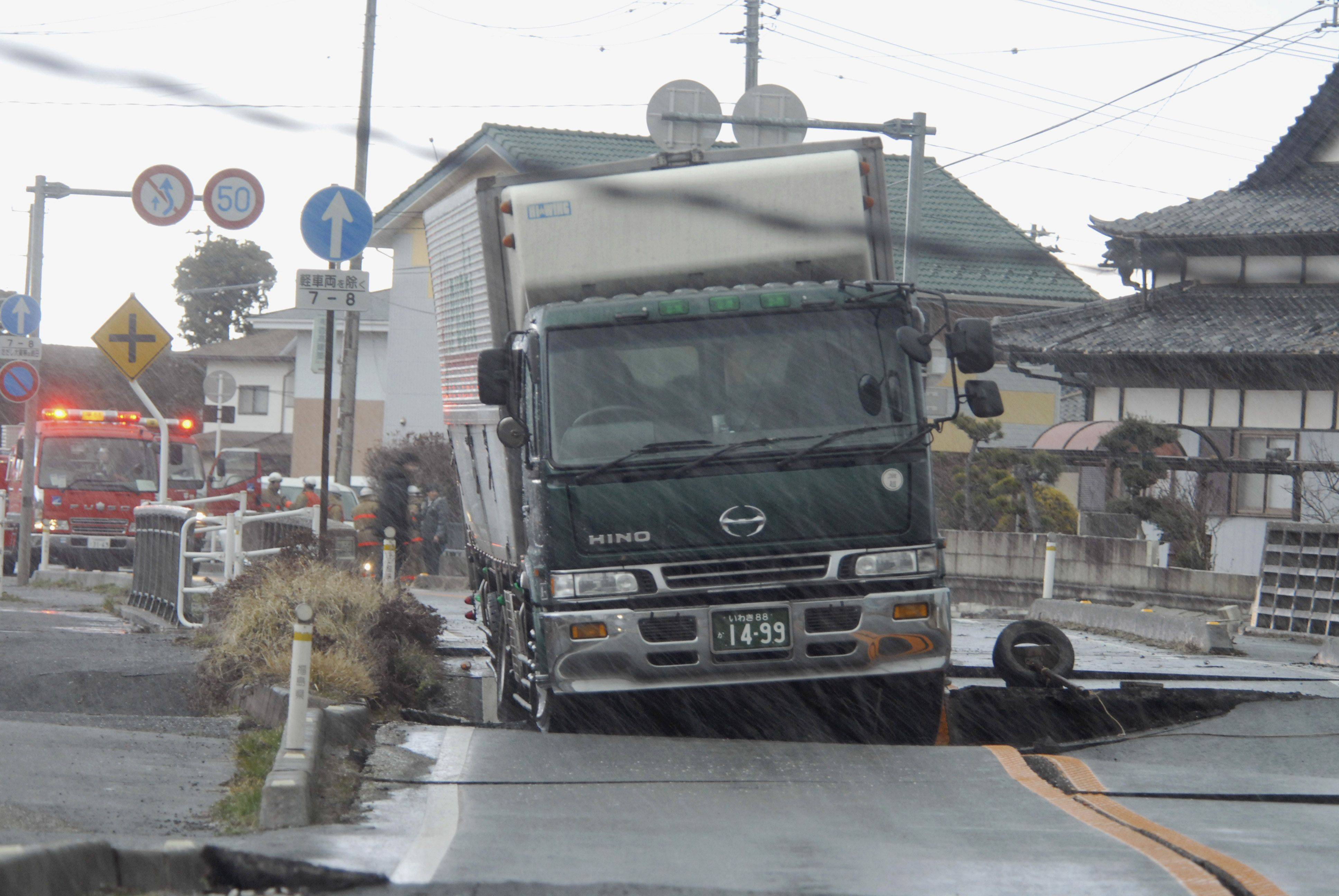 A truck remains stranded on a road damaged by a powerful earthquake in Iwaki city, Fukushima prefecture (state), Japan, Friday.