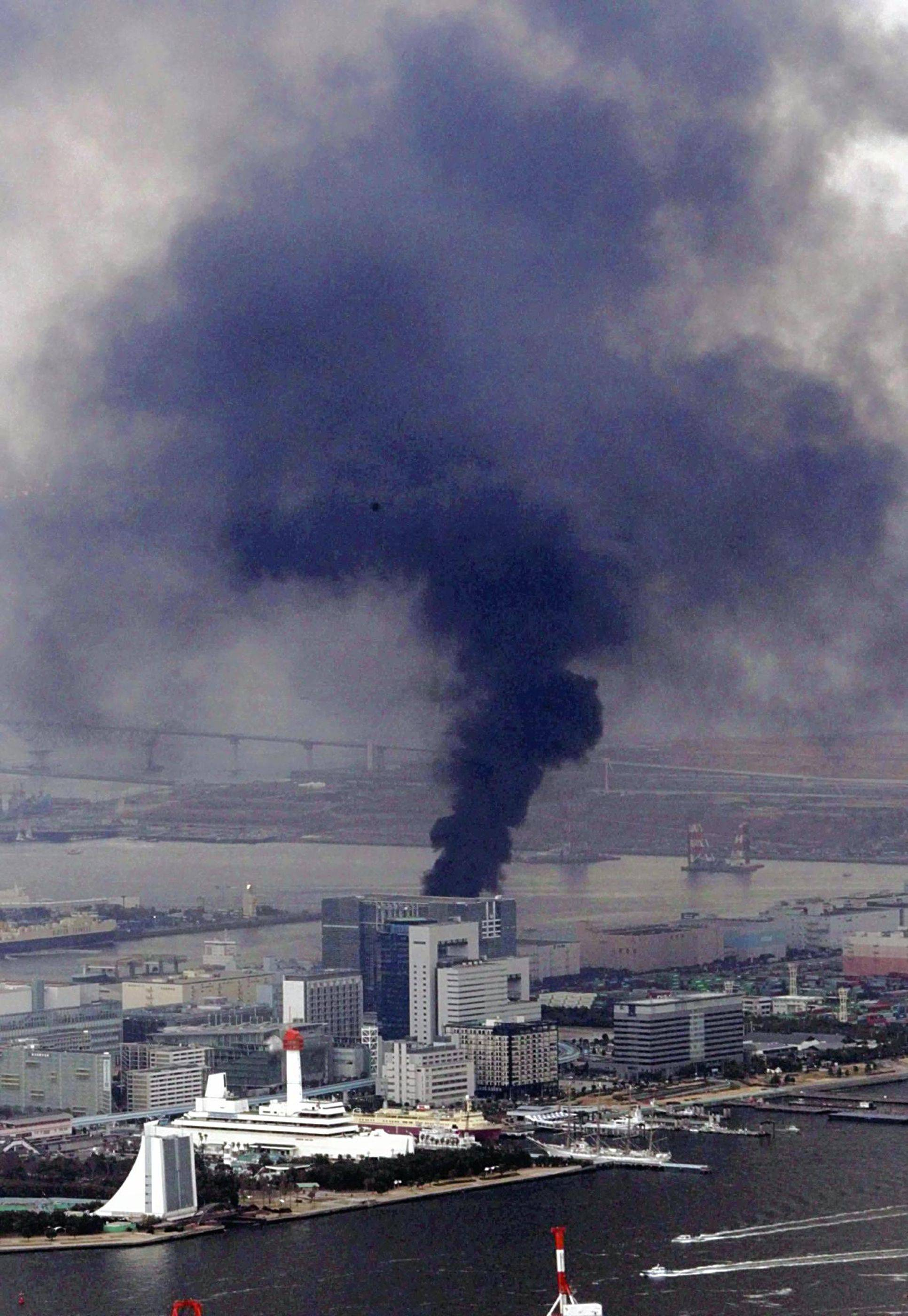 Black smoke rises from a building in Tokyo's Odaiba bay area after strong earthquakes hit Japan Friday.