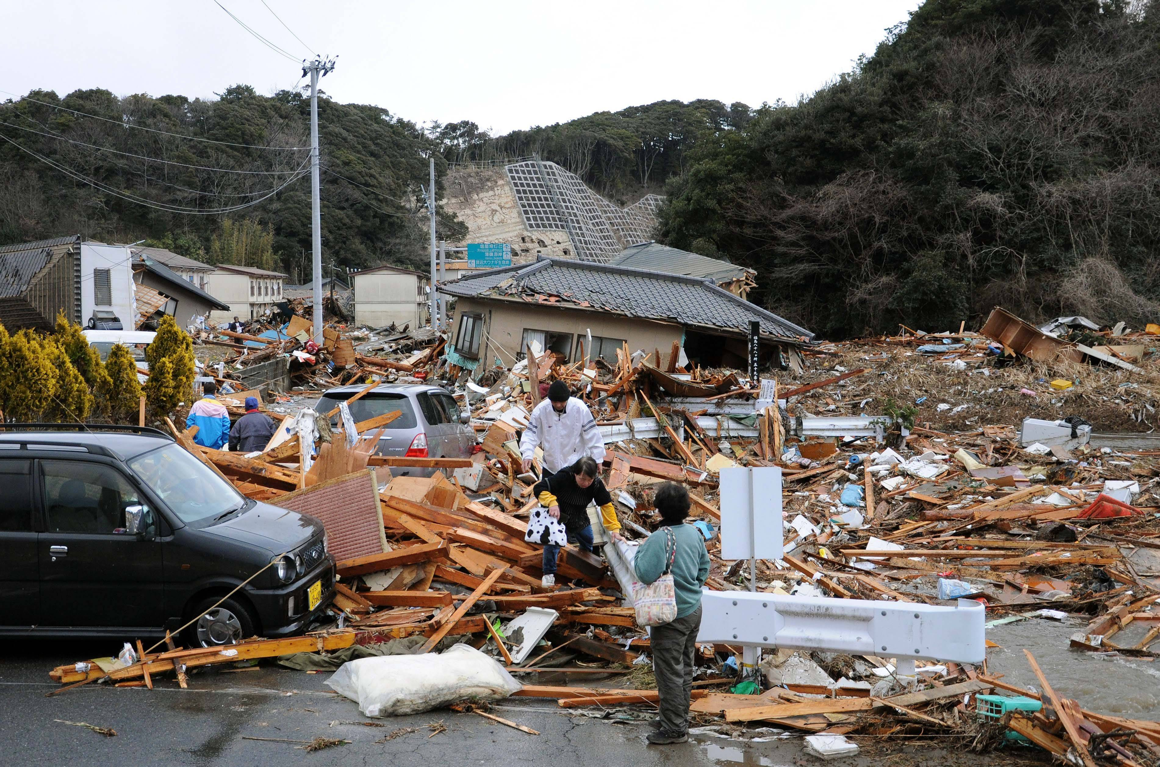 Residents walk through the rubles of residents collapsed by a powerful earthquake in Iwaki, Fukushima prefecture (state), Japan, Friday.