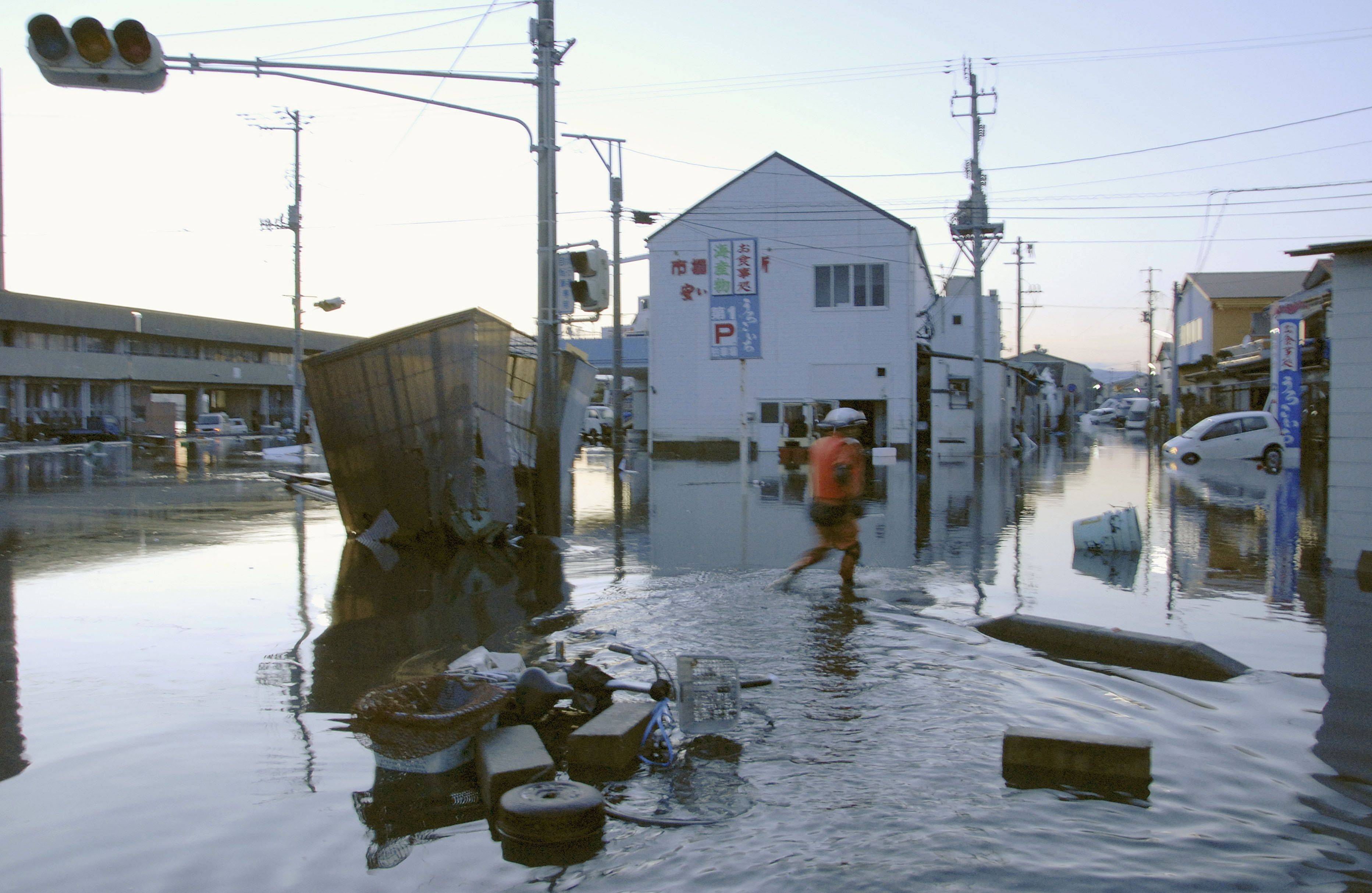 A man wades through a flooded street after tsunami spawned by a powerful earthquake in Iwaki, Fukushima prefecture (state), Japan.