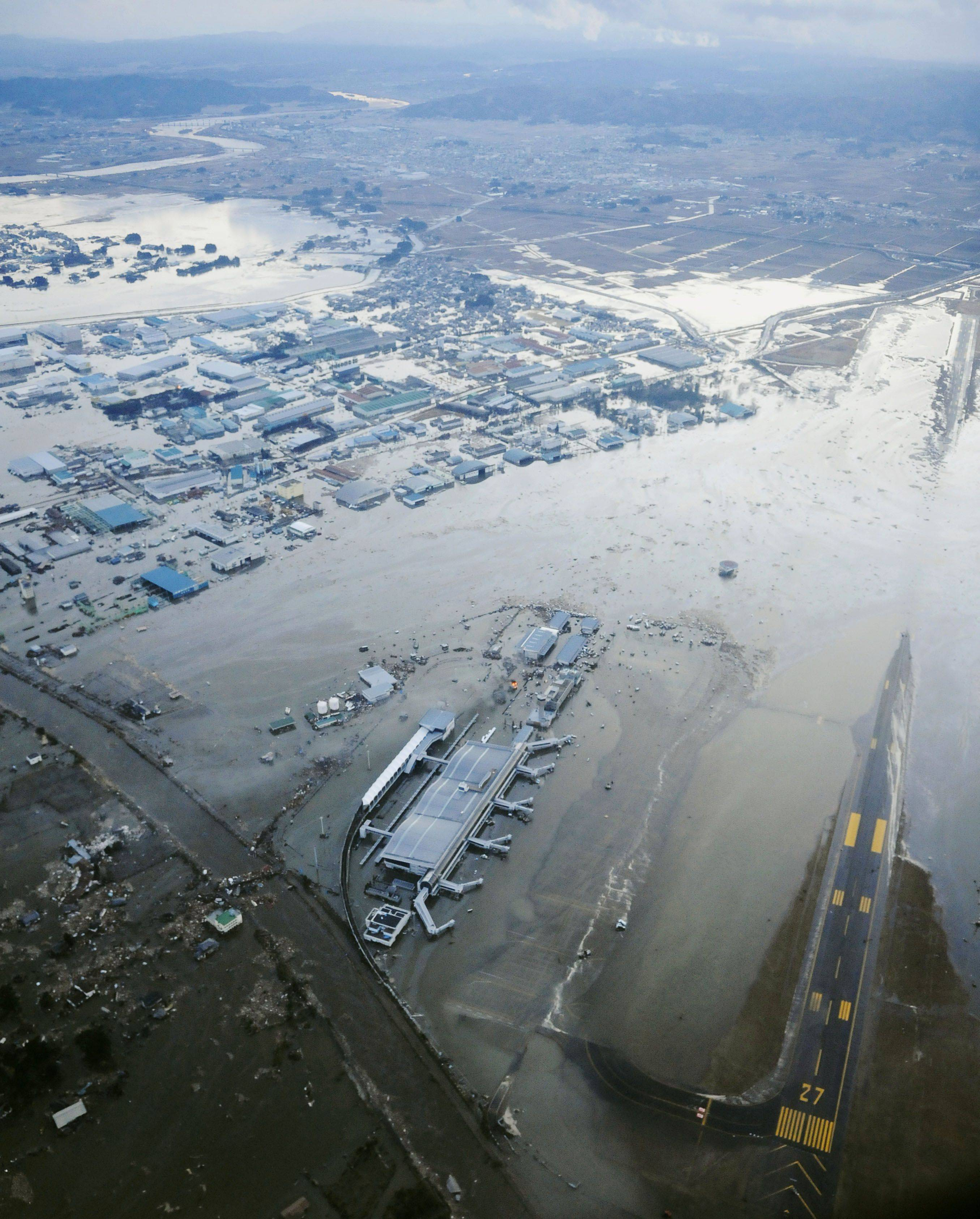 Tarmac and surrounding area are covered with water from tsunami at Sendai Airport in Sendai, Miyagi Prefecture (state).