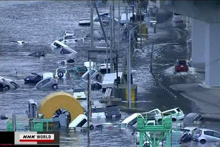 In this video image taken from Japan's NHK TV, cars are washed away in a coastal area of Kamaishi, Iwate prefecture Japan Friday.
