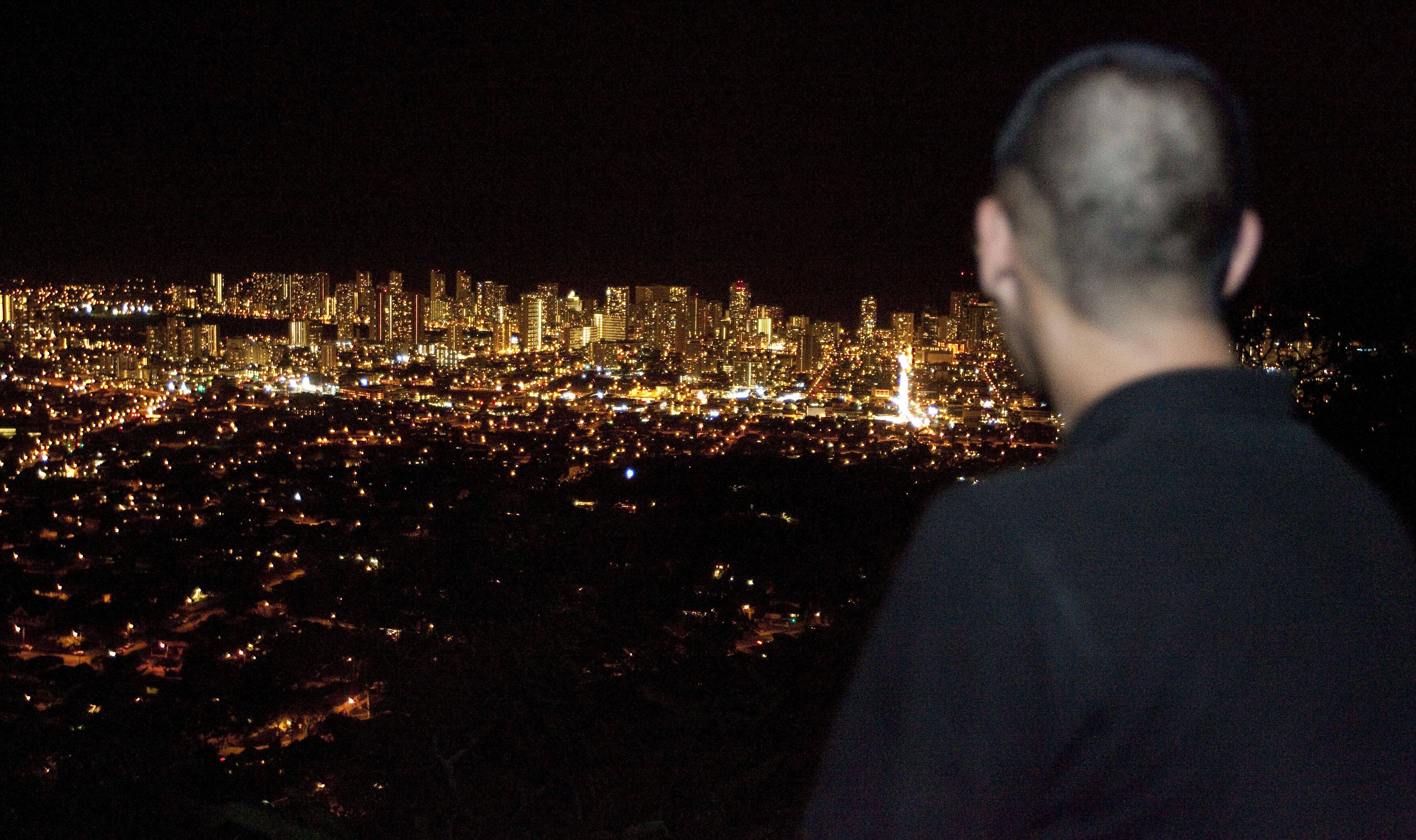 Dain Okimoto looks down on the lights of Waikiki from Tantalus Drive Thursday, March 10, 2011 in Honolulu. Okimoto along with thousands of Oahu residents evacuated to higher ground due to a tsunami warning for the state of Hawaii.,
