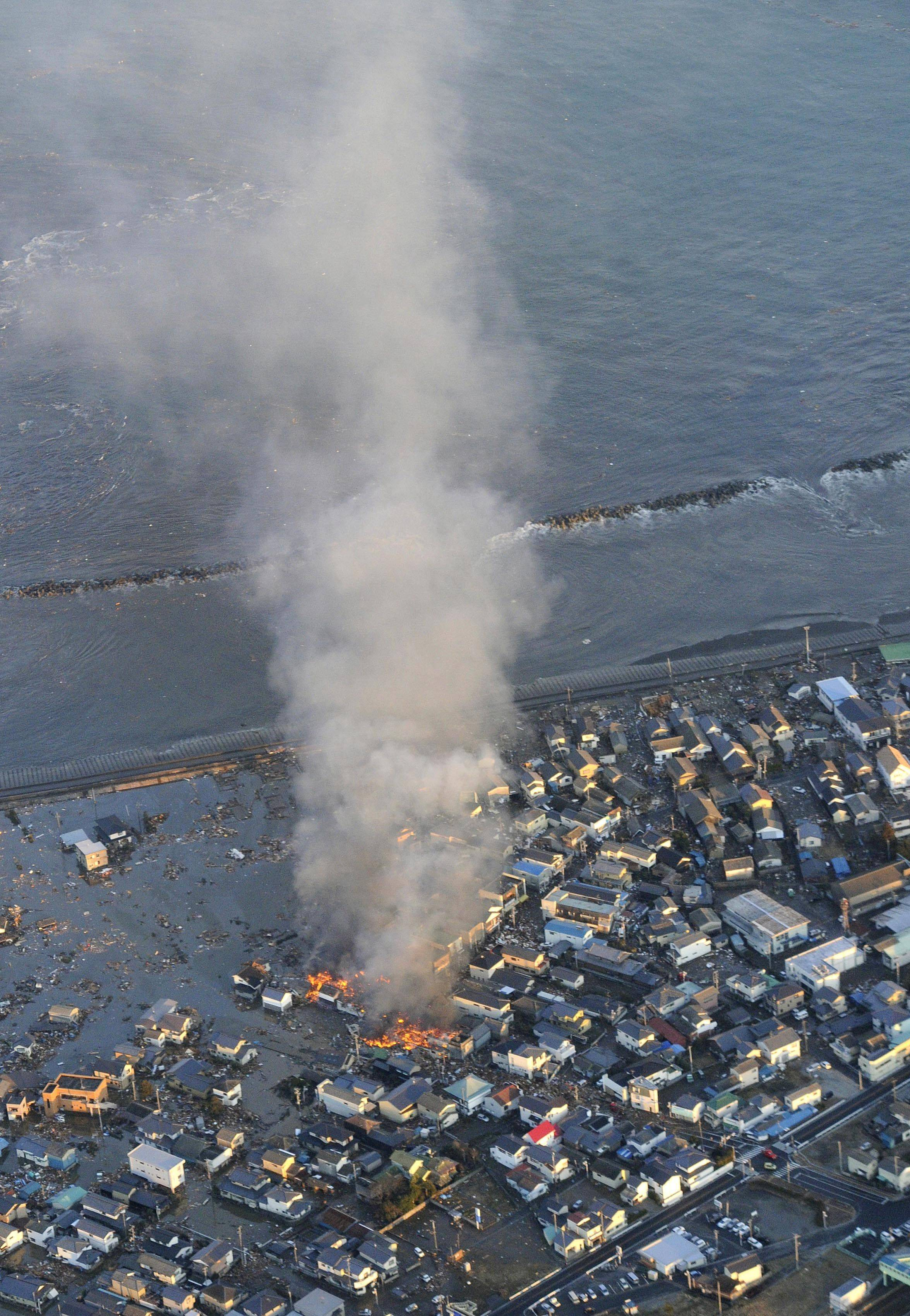 Fire smokes billow from residences as a coastal area is flooded by waters after a tsunami in Iwaki, Fukushima prefecture (state), Japan.