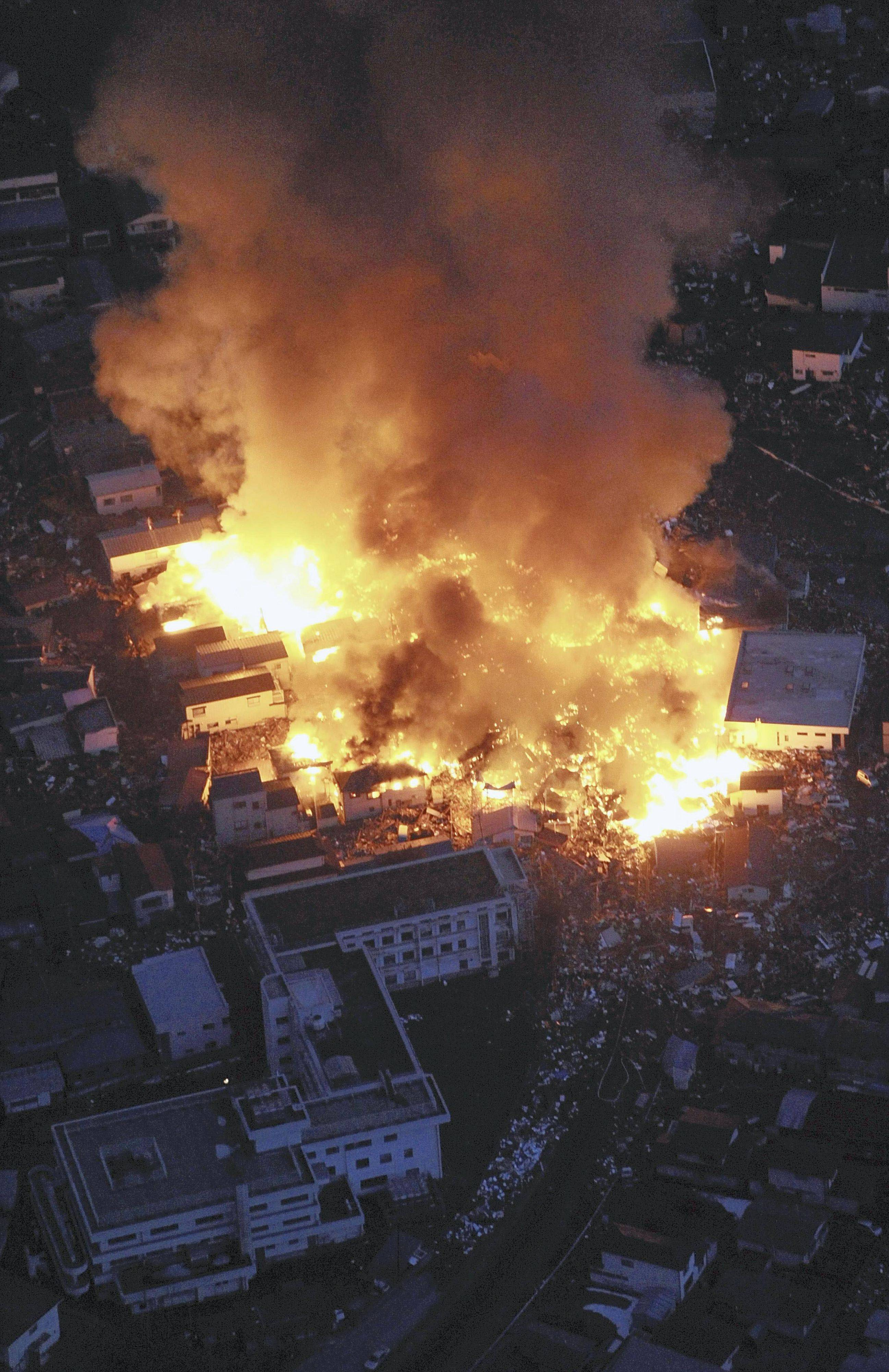 Flames rise from houses on fire after powerful earthquakes hit Yamada, Iwate Prefecture, northern Japan, Friday, March 11, 2011.
