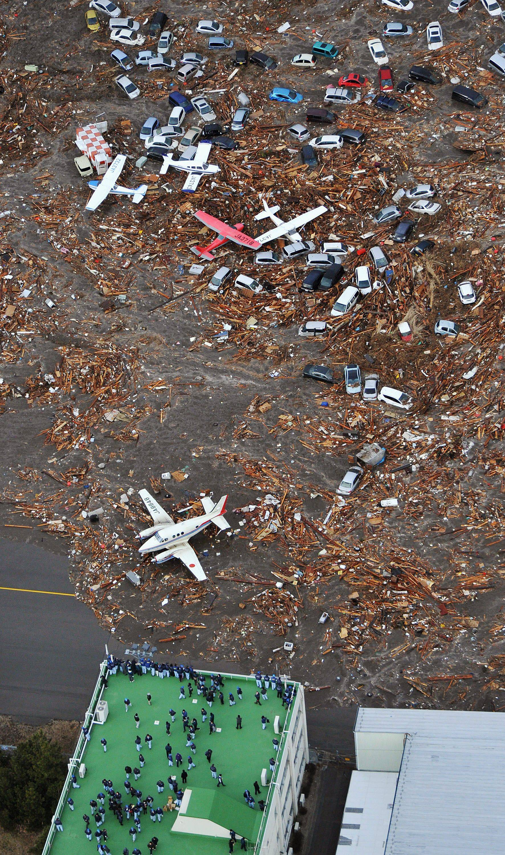 People seek refuge on the rooftop of a building as light planes and vehicles sit among the debris after they were swept by a tsumani that struck Sendai airport in northern Japan.