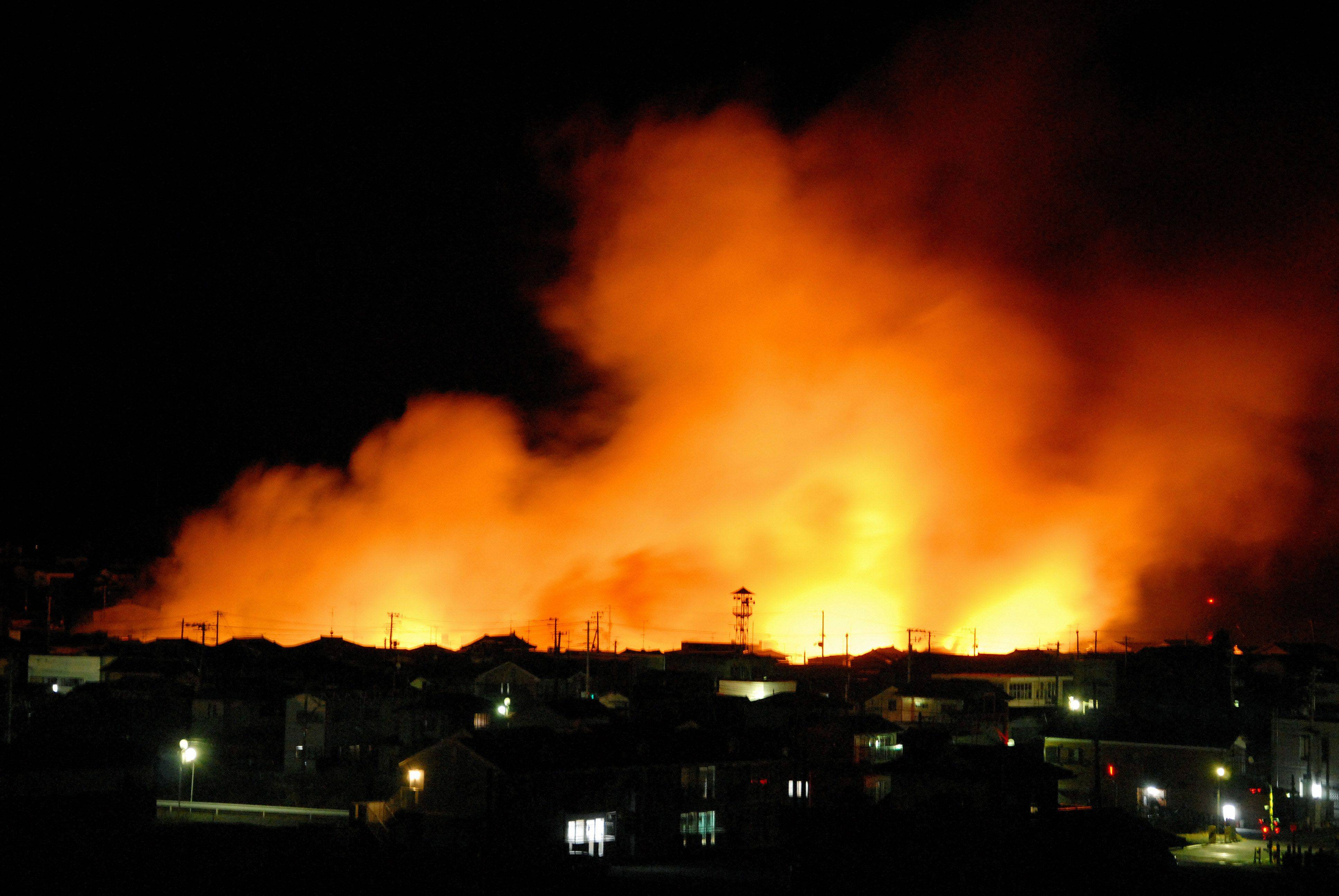Fire flames raise from a coastal area after a powerful earthquake in Iwaki city, Fukushima prefecture (state), Japan.