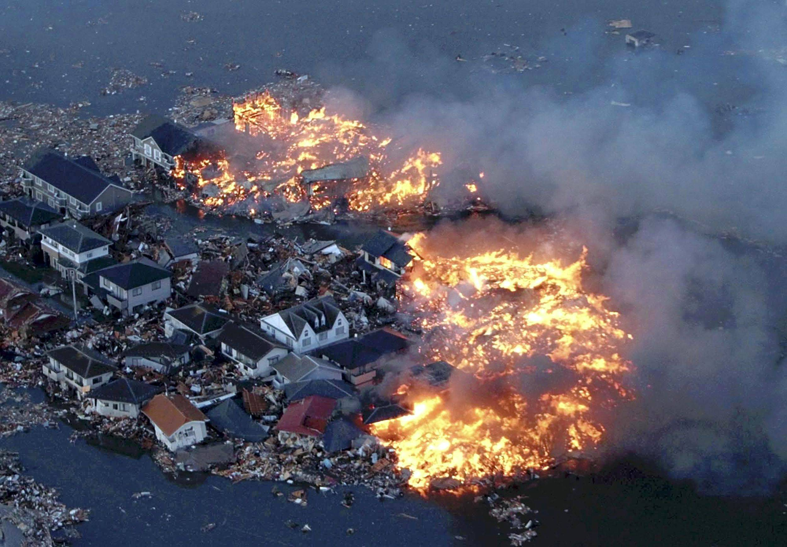 Houses are in flame while the Natori river is flooded over the surrounding area by tsunami tidal waves in Natori city, Miyagi Prefecture, northern Japan.