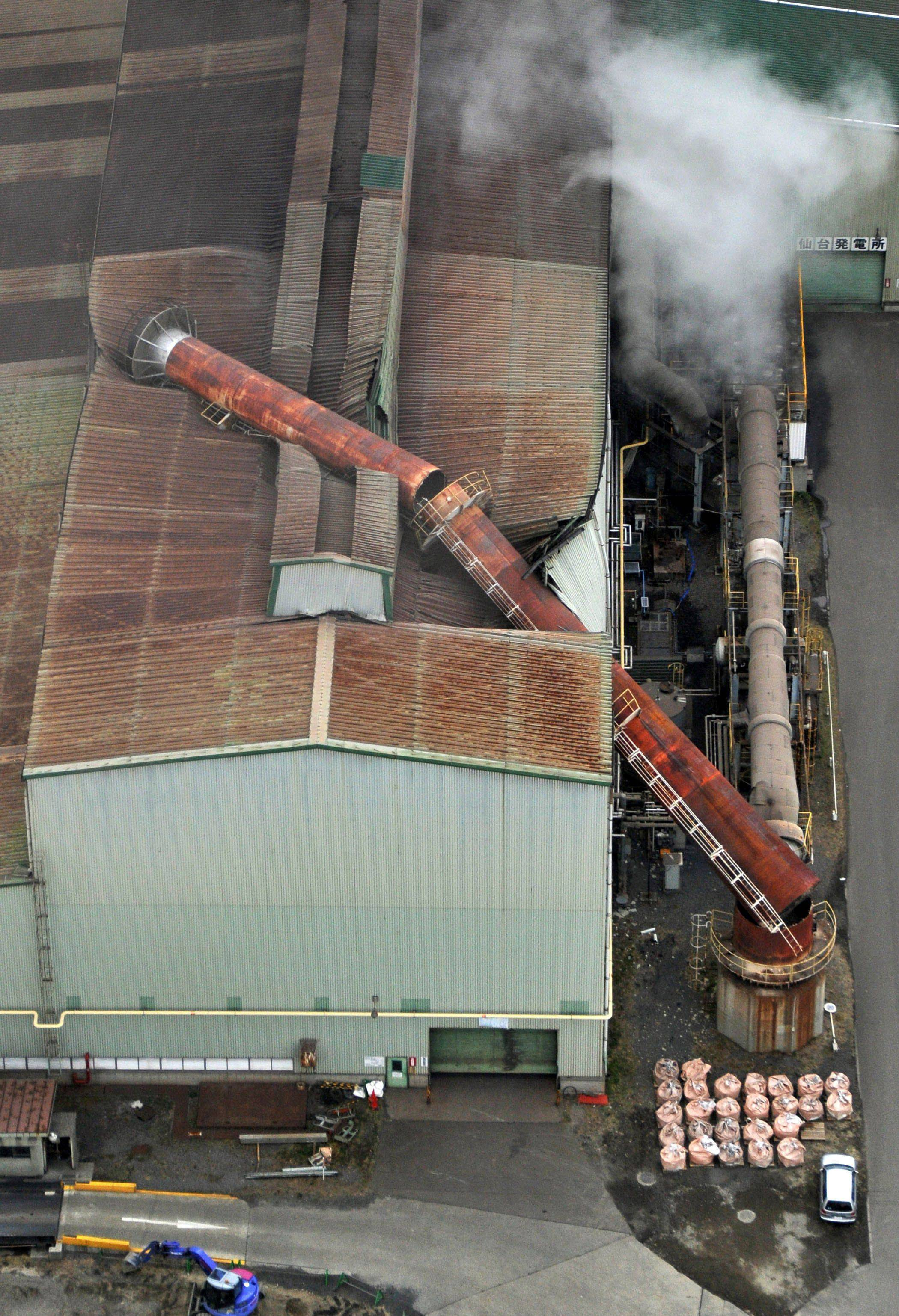 A chimney falls onto its factory in Sendai, Miyagi prefecture (state), Japan, after one of the largest earthquakes on record slammed Japan's eastern coasts Friday, March 11, 2011.