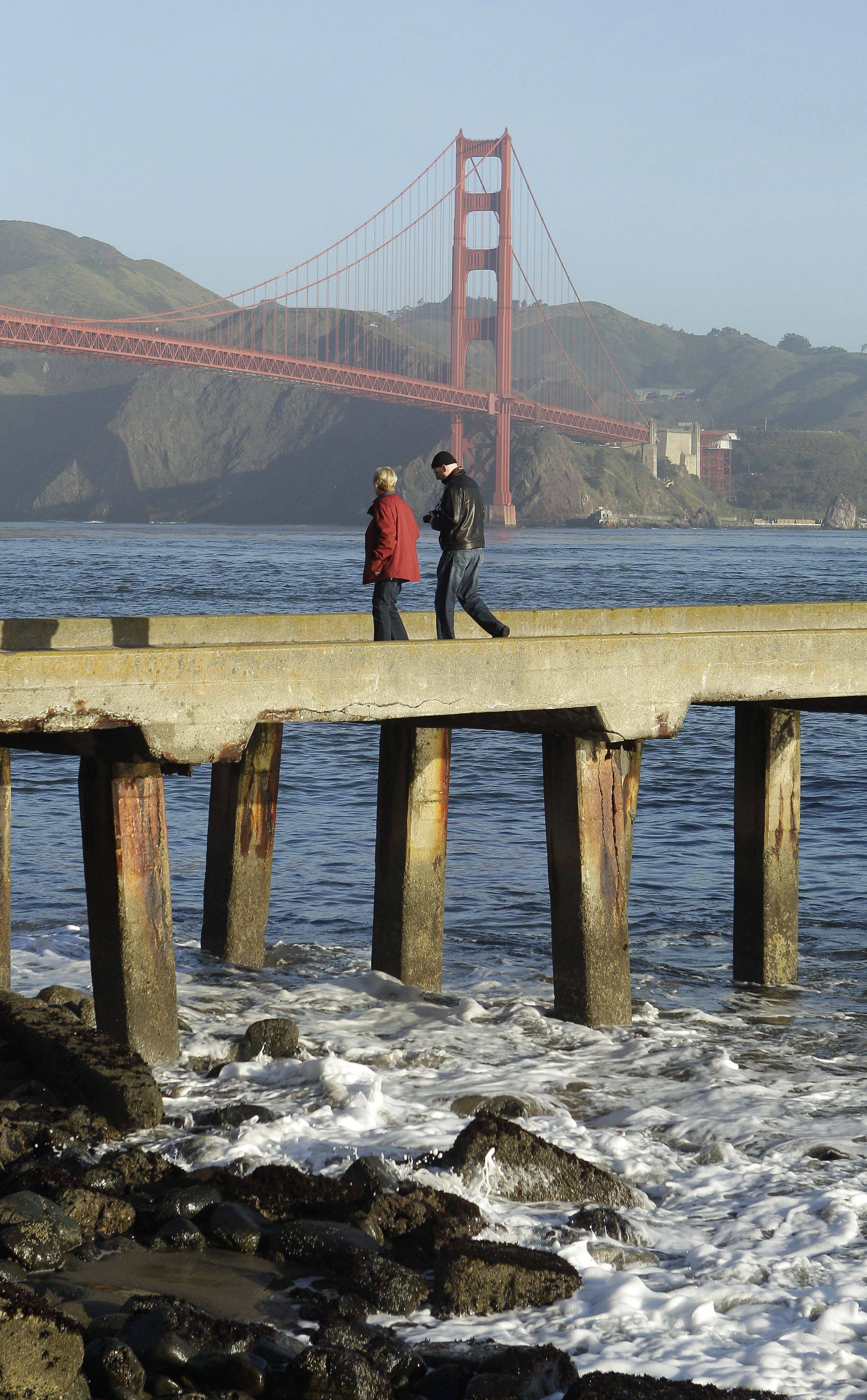 With a tsunami warning in effect for Northern California, a man and woman walk along a pier at Fort Point near the Golden Gate Bridge in San Francisco on Friday, March 11, 2011. The warnings came after a 8.9-magnitude earthquake and a tsunami struck Japan.
