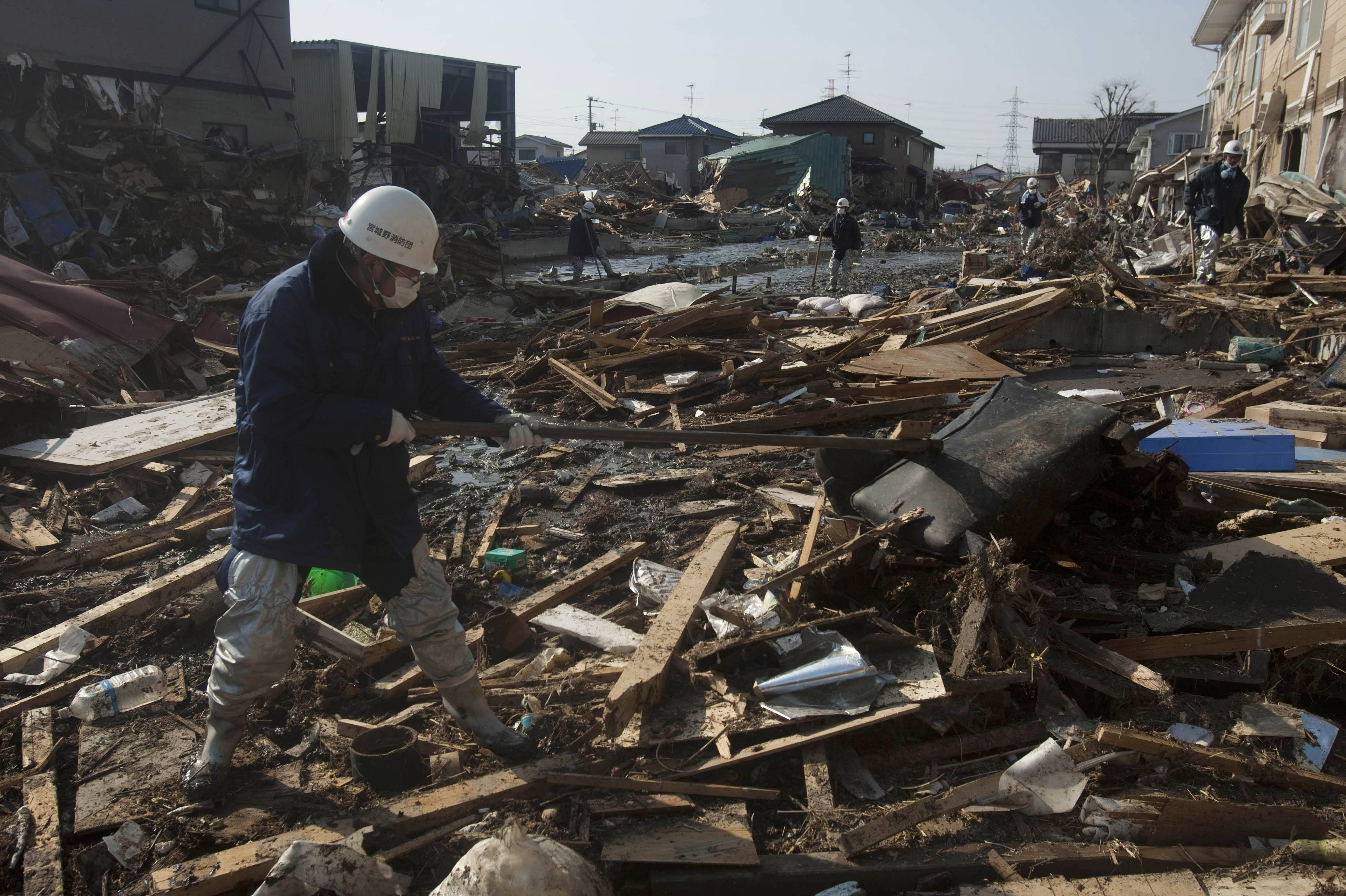 Japanese recovery teams search a destroyed area of Sendai, northeastern Japan, Sunday, March 13, 2011, two days after the area was hit by Friday's catastrophic earthquake-triggered tsunami.