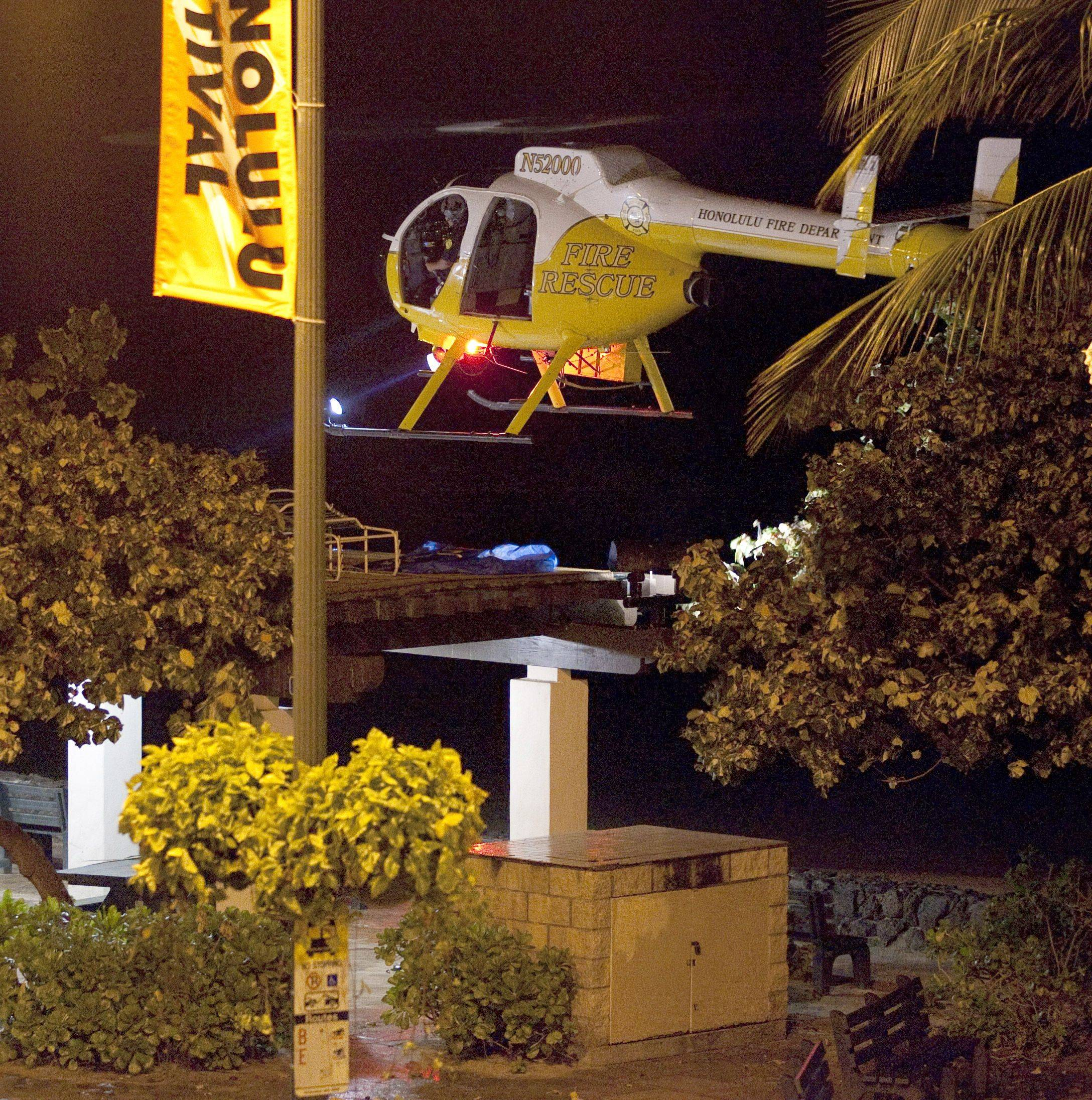 A Honolulu Fire Department helicopter hovers low over Waikiki Beach attempting to chase away some people who had wandered onto the beach early Friday morning, March 11, 2011 in Honolulu.