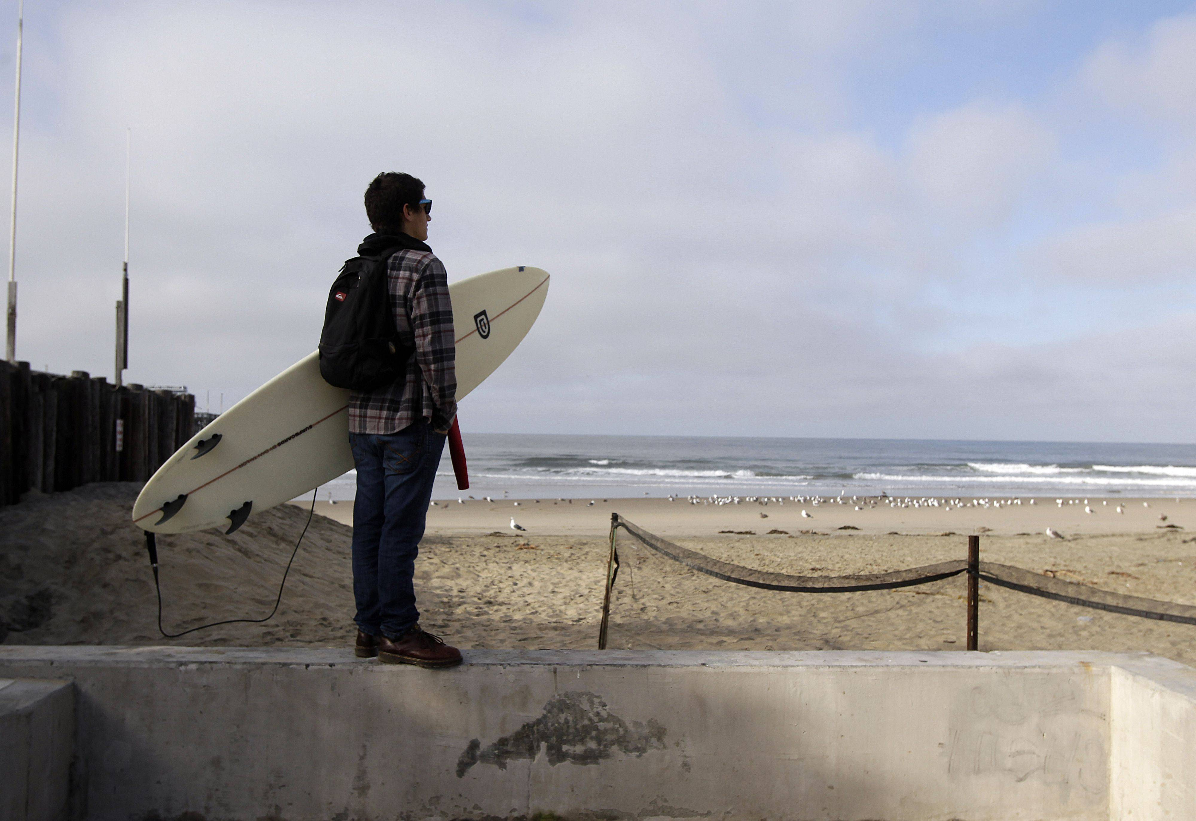 Mark Fontes, of Costa Mesa, Calif., holds his board while watching waves on the Balboa Peninsula in Newport Beach, Calif., Friday, March 11, 2011. An 8.9-magnitude earthquake struck Japan sparking tsunami warnings as far away as the United States' west coast.