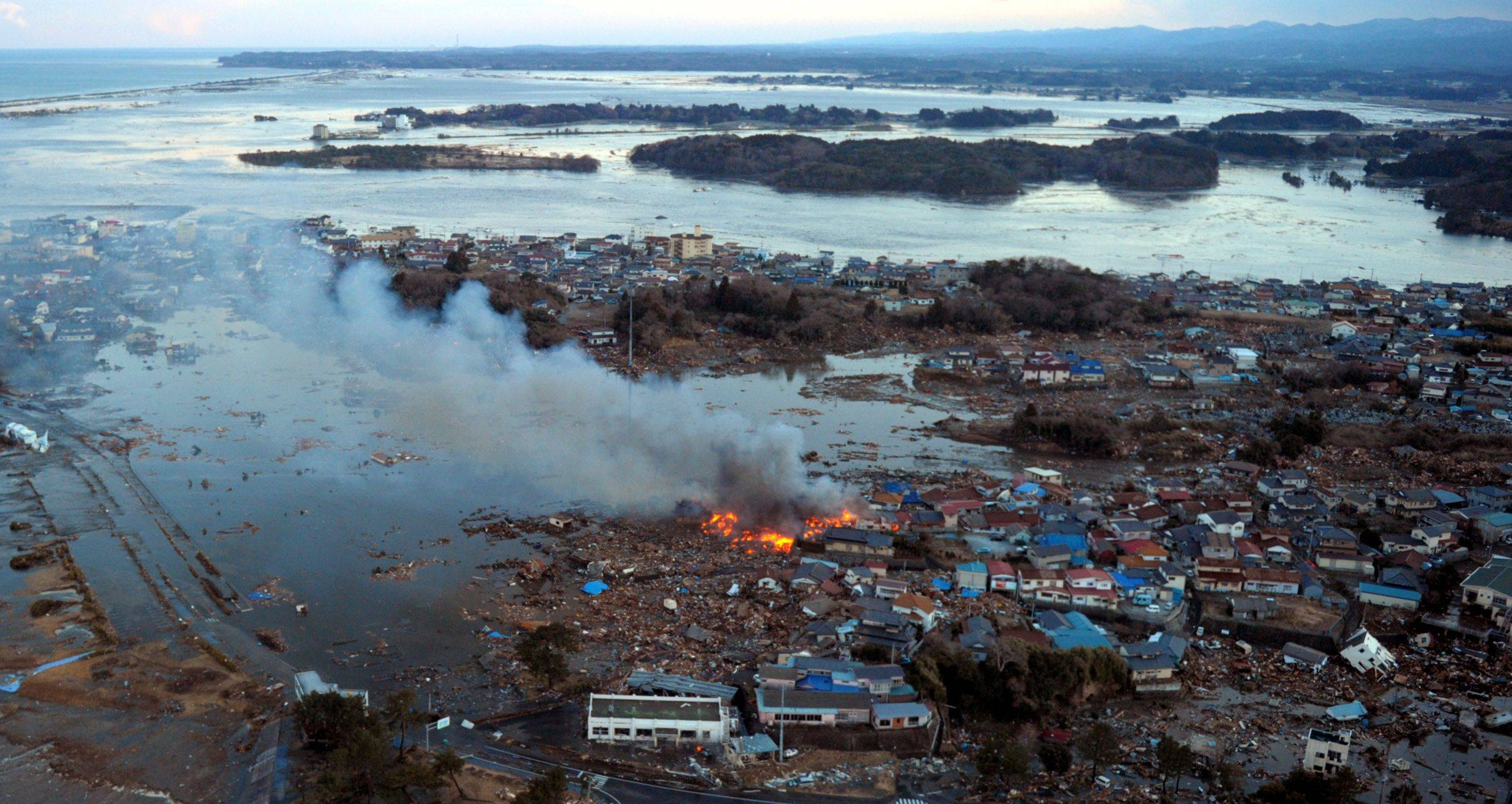 Smoke billows from houses in Natori, northern Japan, after the area was hit by a powerful earthquake and a tsunami on Friday March 11, 2011.