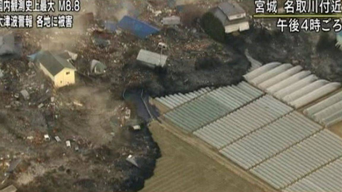 A tsunami surge carrying debris sweeps between houses to reach poly tunnels on farmland near Sendai in Miyagi Prefecture Japan on Friday.