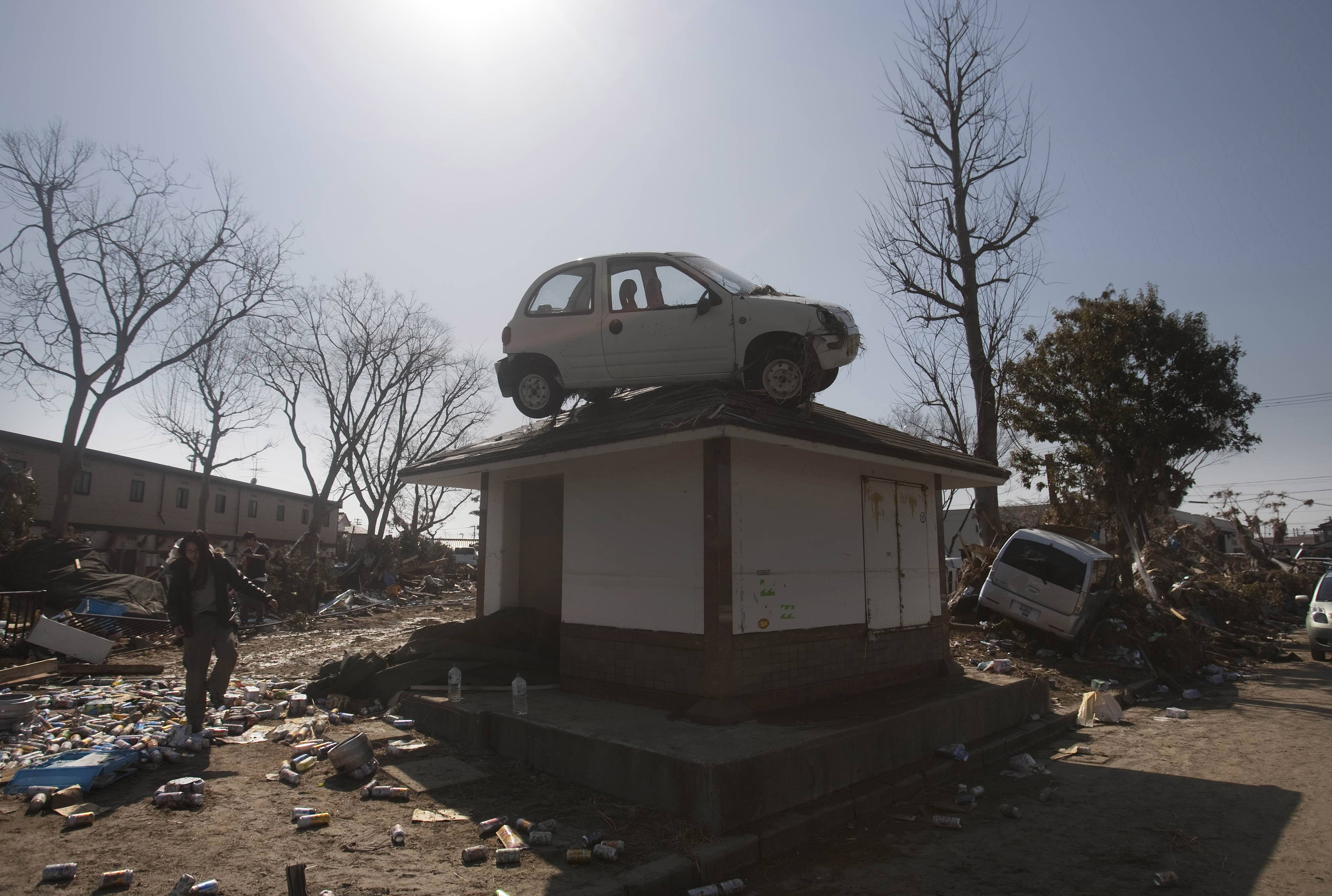 A car sits on top of a small building in a destroyed neighborhood in Sendai, Japan, on Sunday, March 13, 2011 after it was washed into the area by the tsunami that hit northeastern Japan.