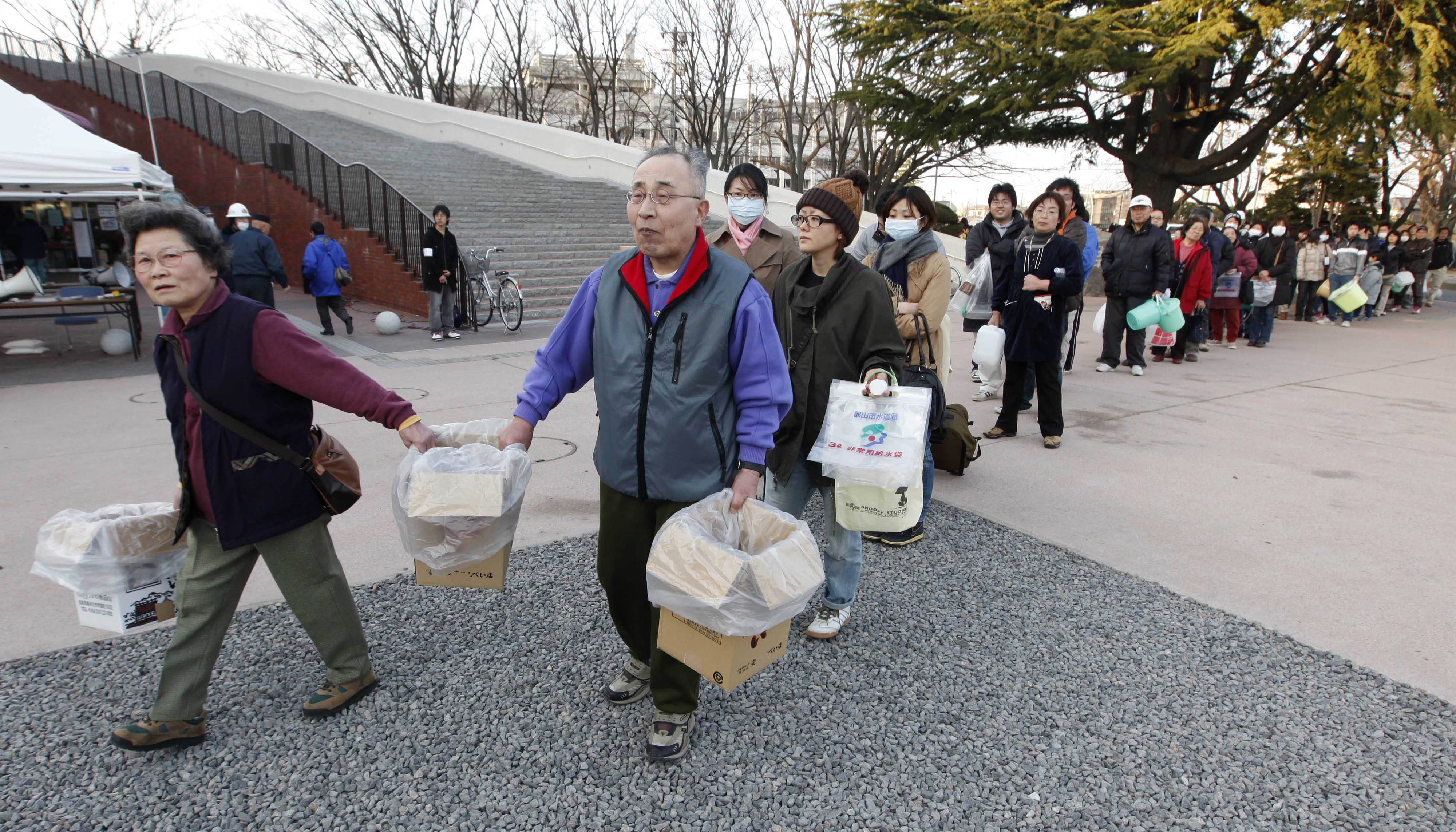 People line up with various containers to get fresh water in Koriyama, Fukushima Prefecture, Japan, Sunday, March 13, 2011, two days after a giant quake and tsunami struck the country's northeastern coast.
