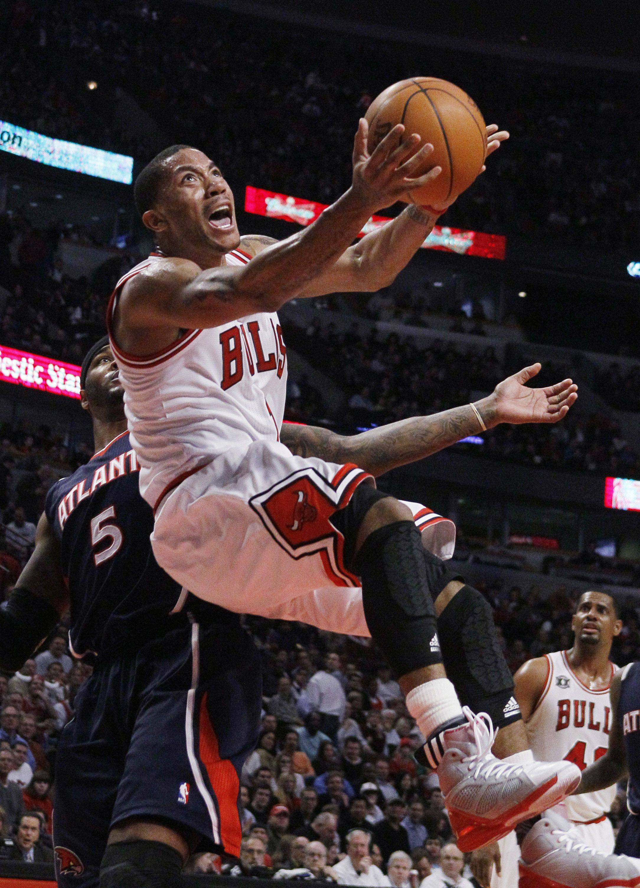 Bulls point guard Derrick Rose, right, scores over Atlanta Hawks power forward Josh Smith, during the second half Friday in Chicago. Rose led all scorers with 34 points in their 94-76 win.
