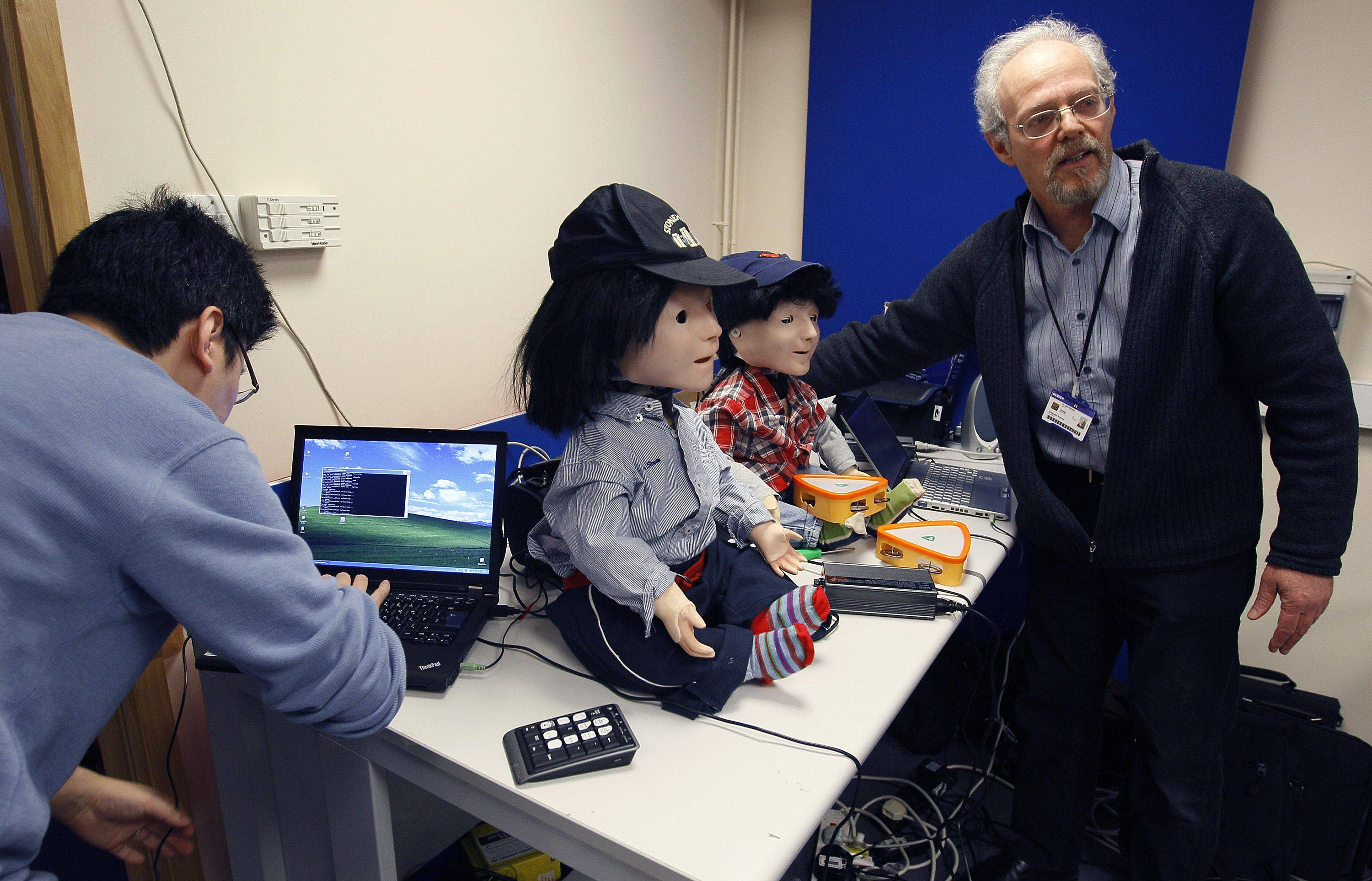 Dr. Ben Robins, right, shows off two Kaspar robots that he hopes will help autistic children. The children play with the robot alongside a scientist who controls it with a remote control.