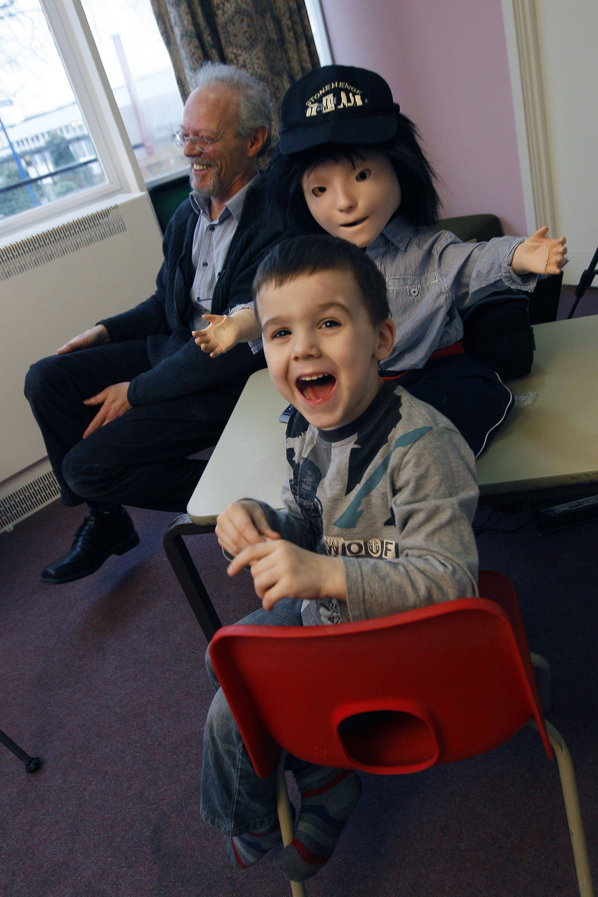 Ronnie Arloff smiles as he reacts to Kaspar the robot as he takes part in a research project with Dr. Ben Robins in Hatfield, England. Autistic children play with the robot for up to 10 minutes alongside a scientist who controls the robot with a remote control.
