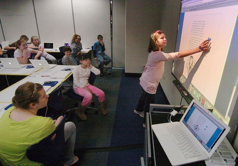 Fifth-grader Sabrina Larbi works on the electronic whiteboard during a reading lesson using Des Plaines Elementary District 62's Technology-Integrated Learning Environment classroom at Cumberland School. District 62 is one of the few suburban districts able to afford such technology upgrades in today's economy.