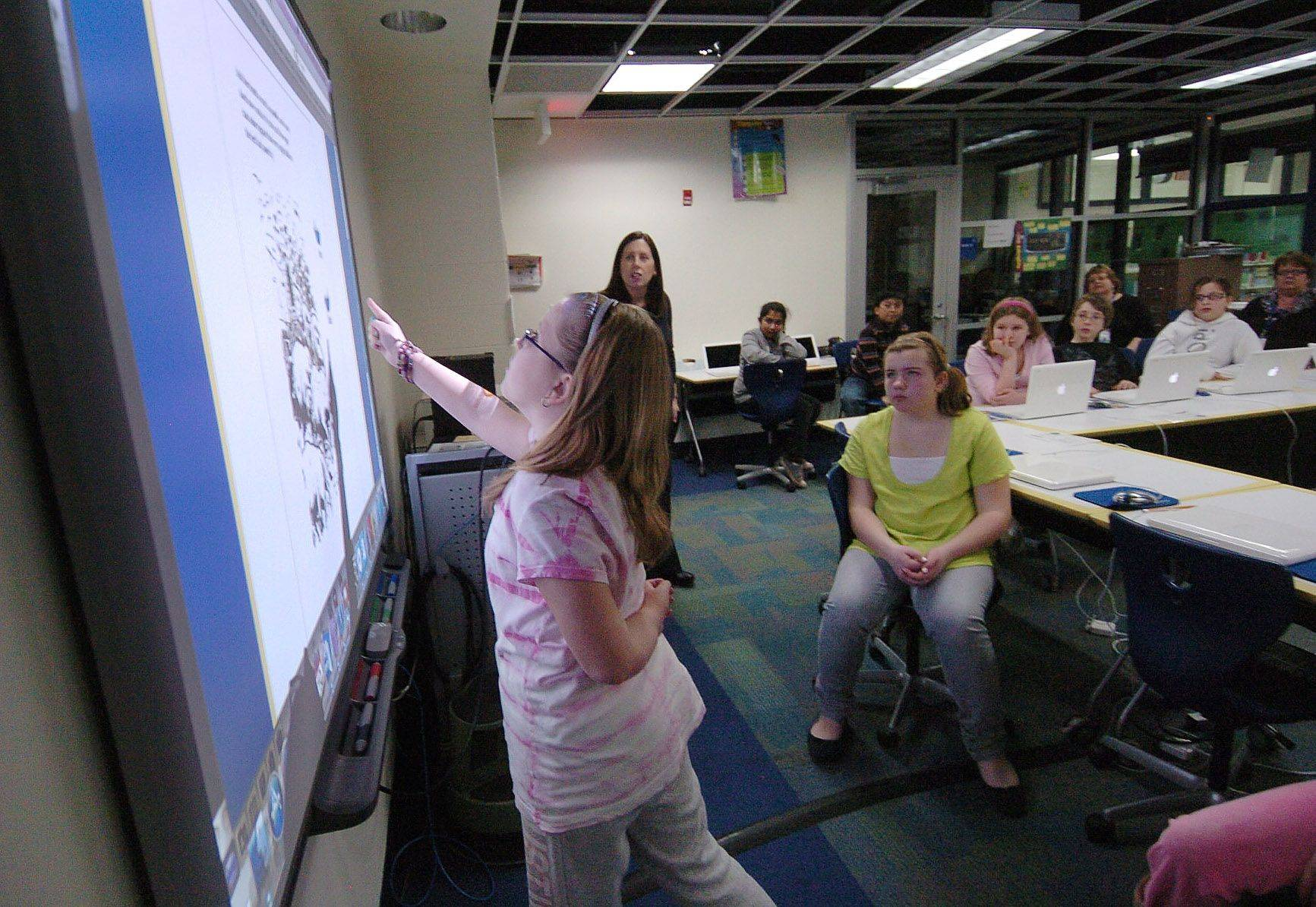 Fifth-grader Emily Modloff uses the electronic whiteboard during a reading lesson in Des Plaines Elementary District 62's Technology-Integrated Learning Environment classroom at Cumberland School in Des Plaines. District 62 is one of the few suburban districts able to afford such technology upgrades in today's economy.