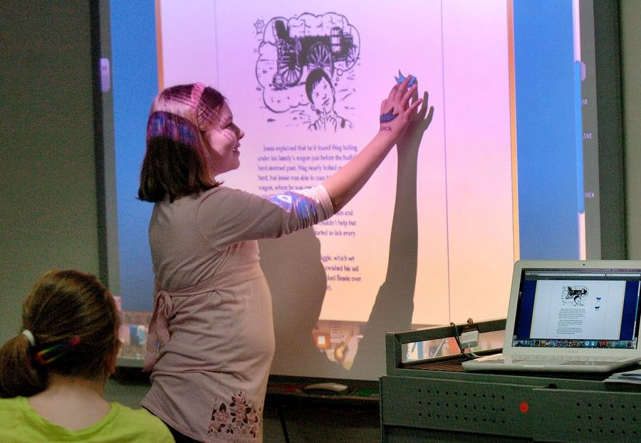 Fifth grader Sabrina Larbi touches the screen of an electronic whiteboard during a reading lesson in Des Plaines Elementary District 62's Technology-Integrated Learning Environment classroom at Cumberland School in Des Plaines. District 62 is one of the few suburban districts able to afford such technology upgrades in today's economy.