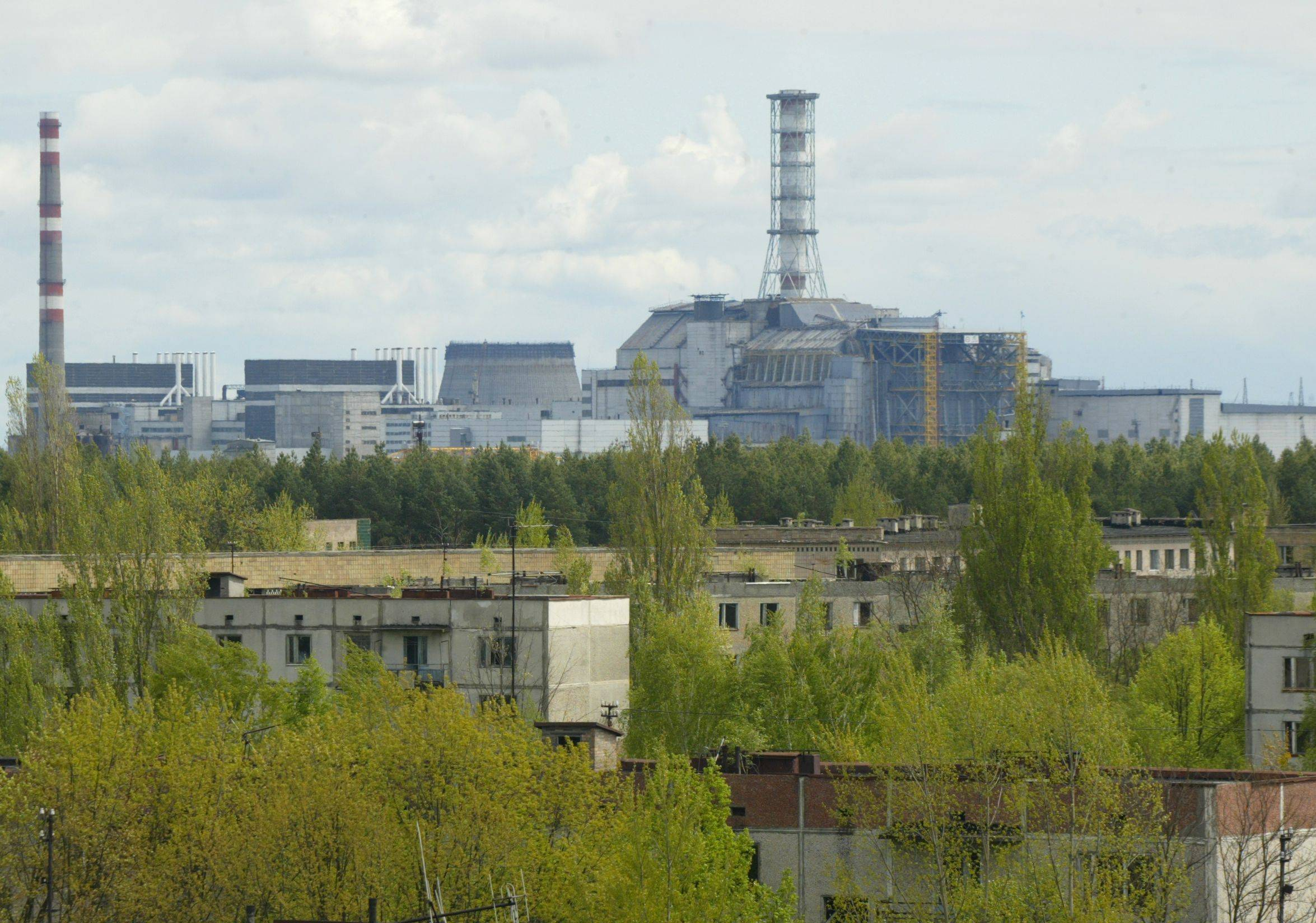 The closed Chernobyl nuclear power plant looms over abandoned houses in the town of Pripyat, which sits inside a contamination zone. A 1986 nuclear catastrophe caused dozens of immediate fatalities and other lingering health problems.