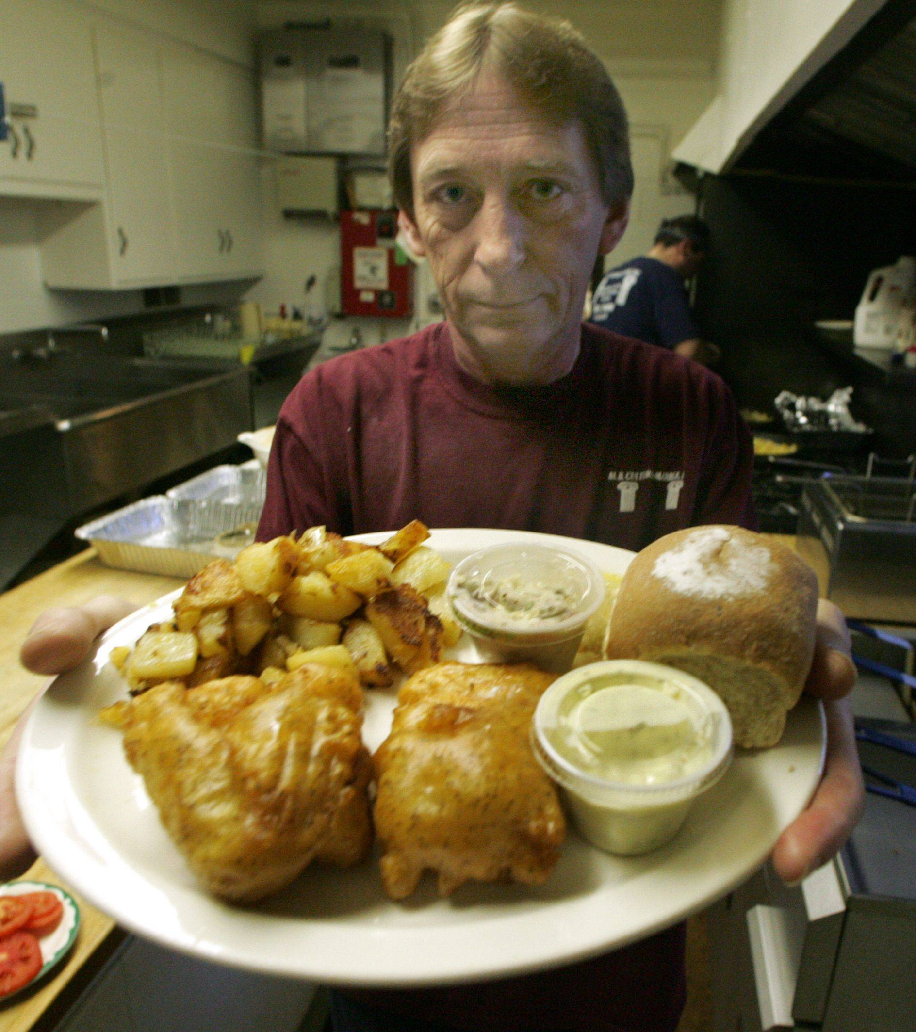 Robbie Robinson shows off a plate of beer-battered Icelandic cod that includes American fries, coleslaw and a roll at VFW Post 2298 in West Dundee.