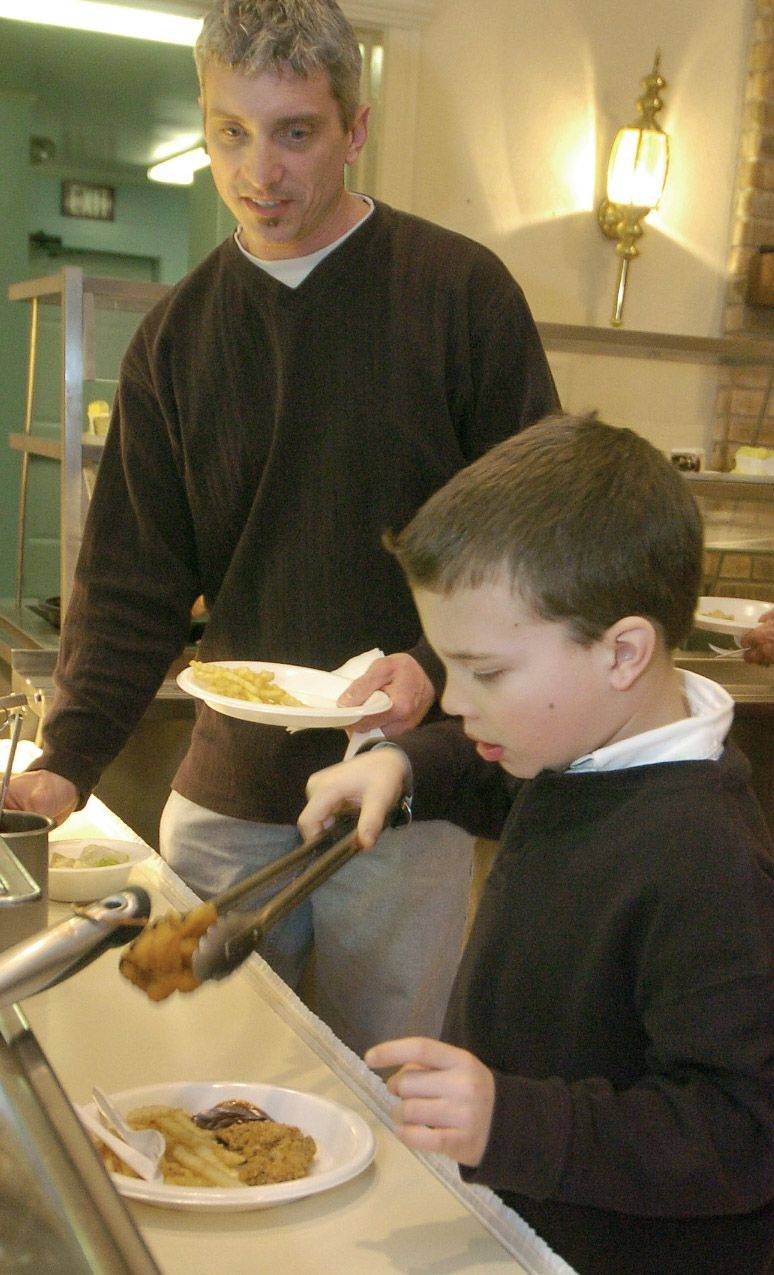 Nathan Huber dishes up some fried shrimp while eating with dad Bill of Batavia at the Geneva American Legion fish fry.