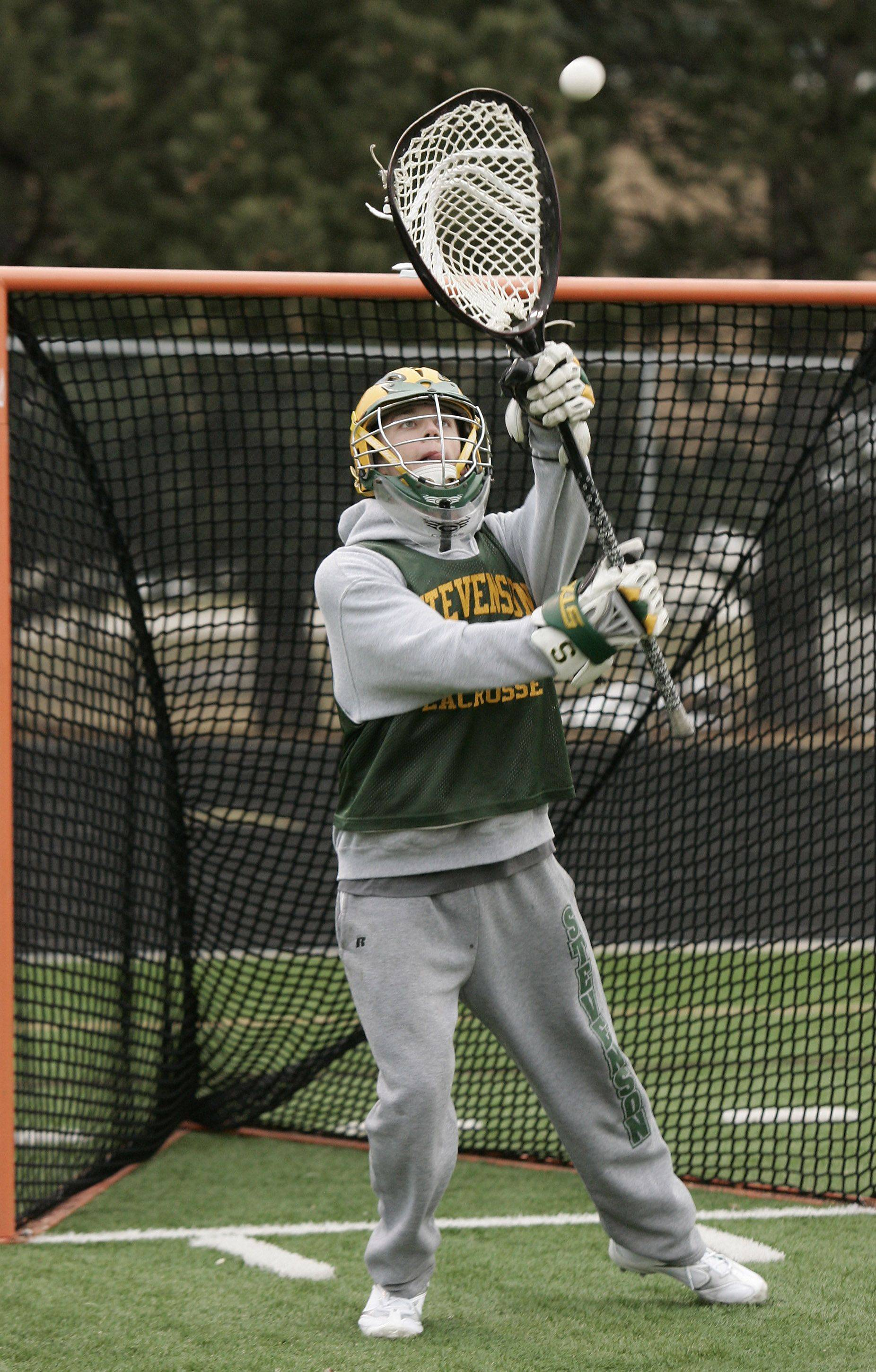 Goalkeeper Max Huber blocks a shot as the boys lacrosse team practice at Stevenson High School in Lincolnshire.