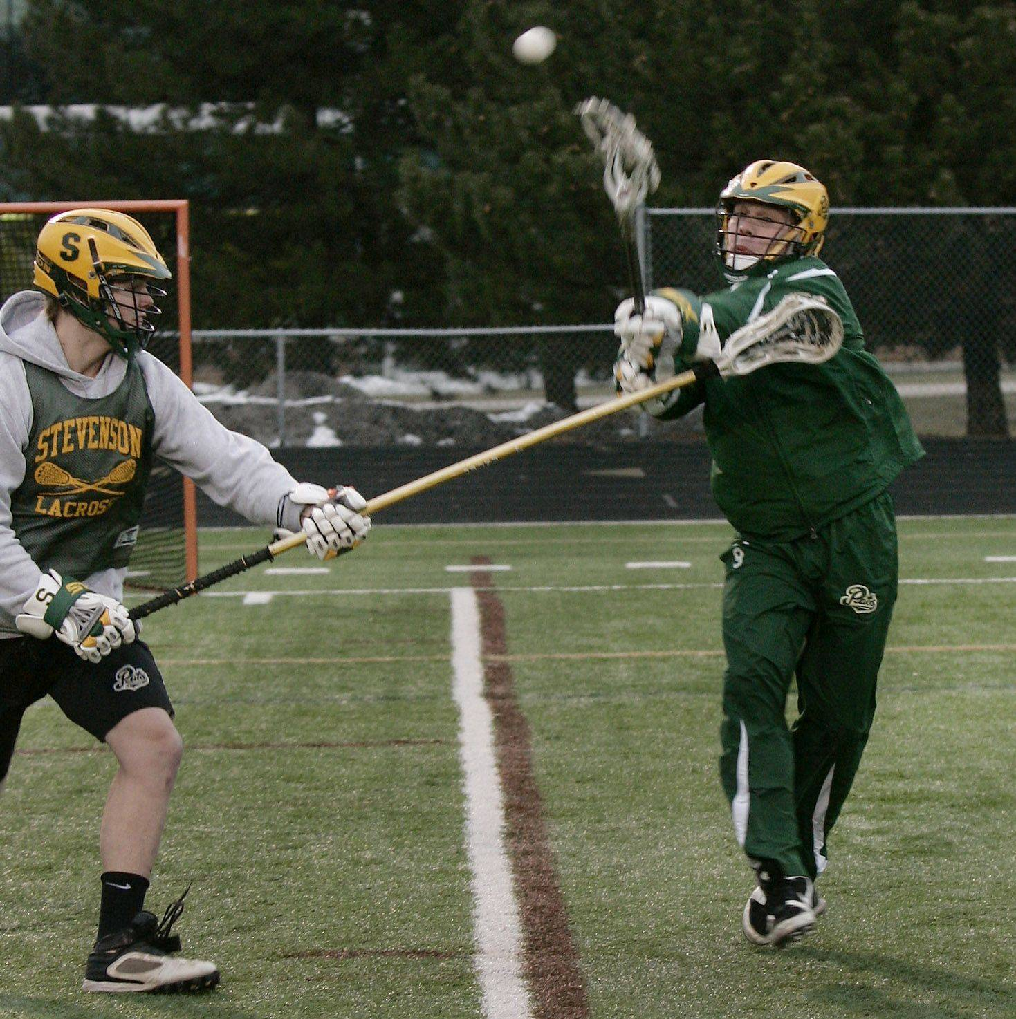 Midfielder Ryan Spitzer passes the ball past defender Eric Brasier during the boys lacrosse team practice at Stevenson High School in Lincolnshire.
