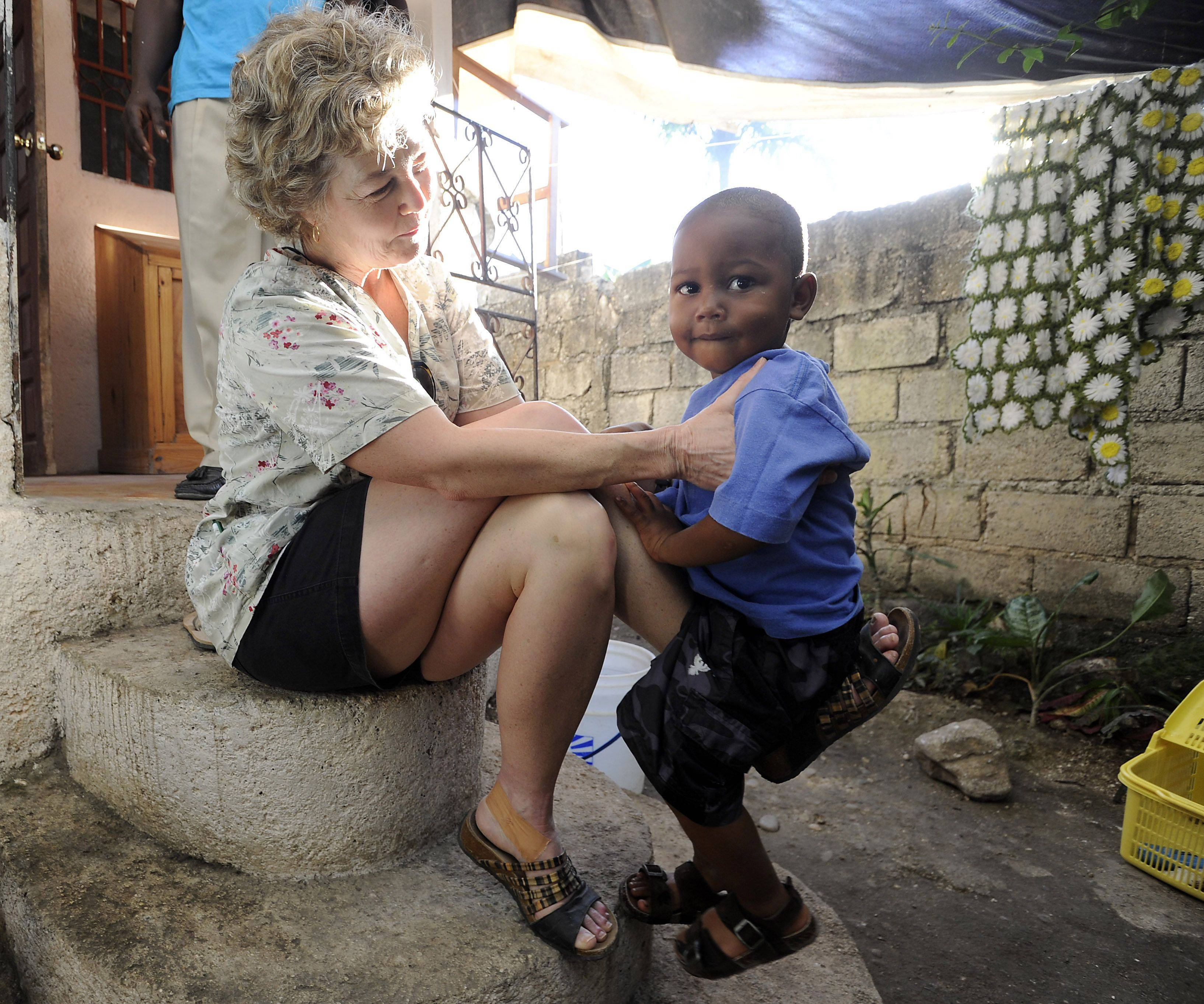 Trudy Vogel plays with Godson, 3, at their home in Jacmel, Haiti.