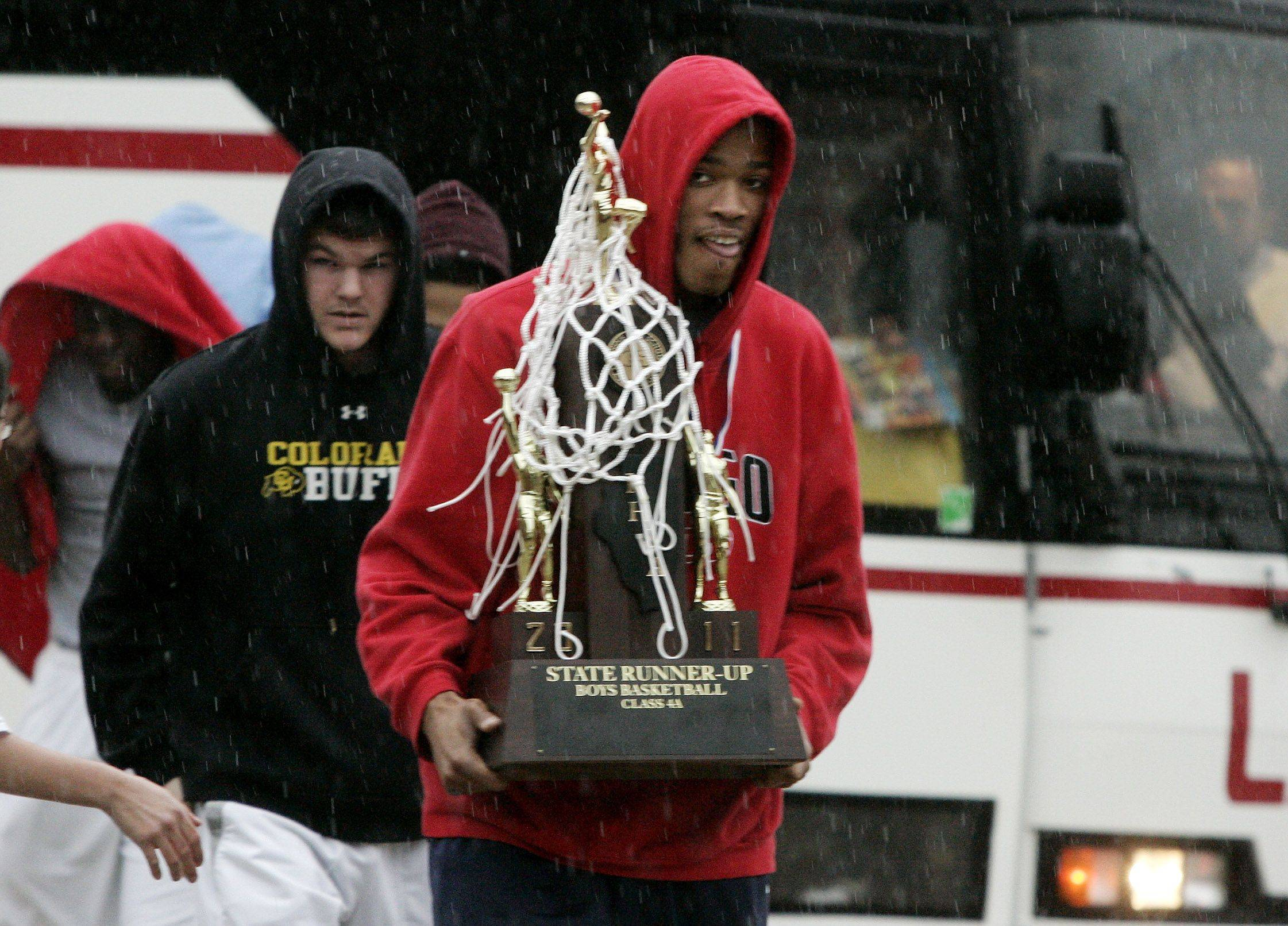Jeremiah Jackson carries the trophy off the bus and into the rain as the Warren Township High School boys basketball team returns to the high school in Gurnee Sunday after finishing second in the state tournament.