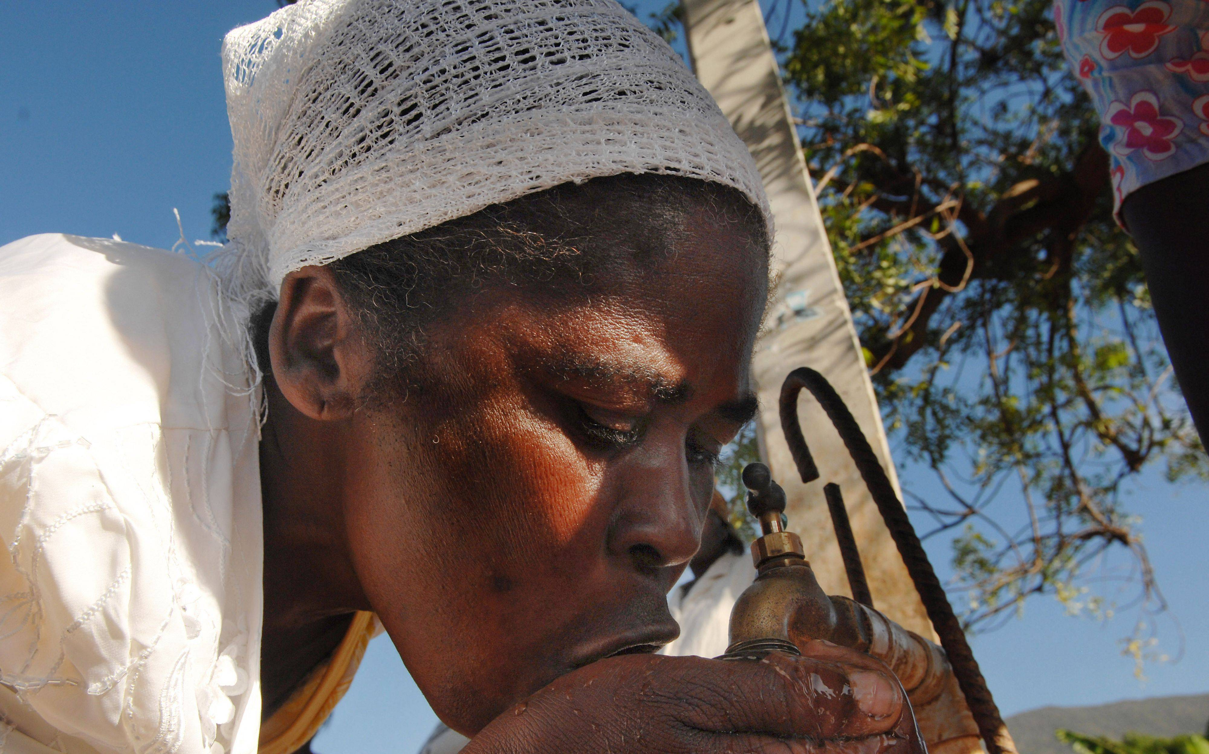 Mark Welsh/mwelsh@dailyherald.comA Haitian woman drinks from a public well in Jacmel, Haiti, south of Port-au-Prince. The well tested positive for E. coli.
