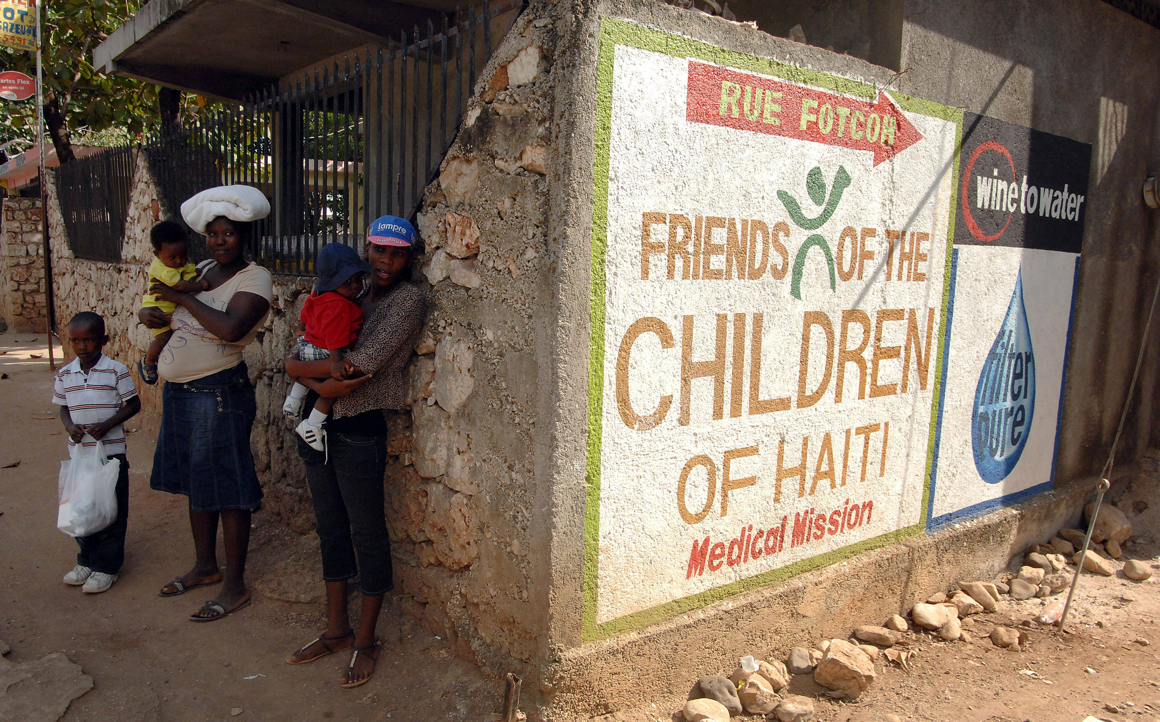 Signs point the way in Jacmel, Haiti to the FOTCOH Clinic and the FilterPure Filters factory as Haitians wait for a ride after visiting the clinic for medical care.