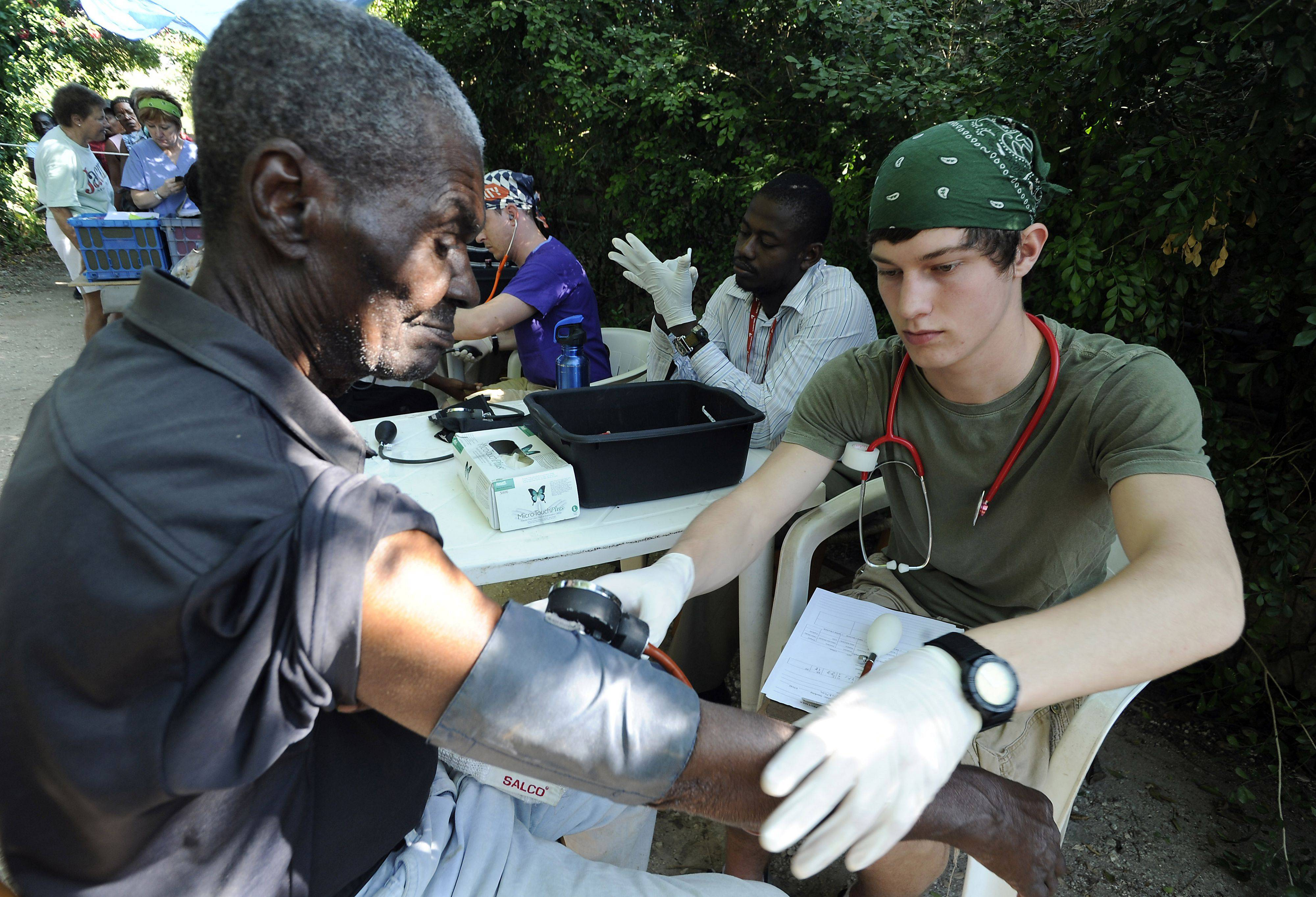 Josiah Ballantine, 18, of Elk Grove Village takes the blood pressure of a Haitian man at the Friends of the Children of Haiti clinic in Cyvadier, Haiti.