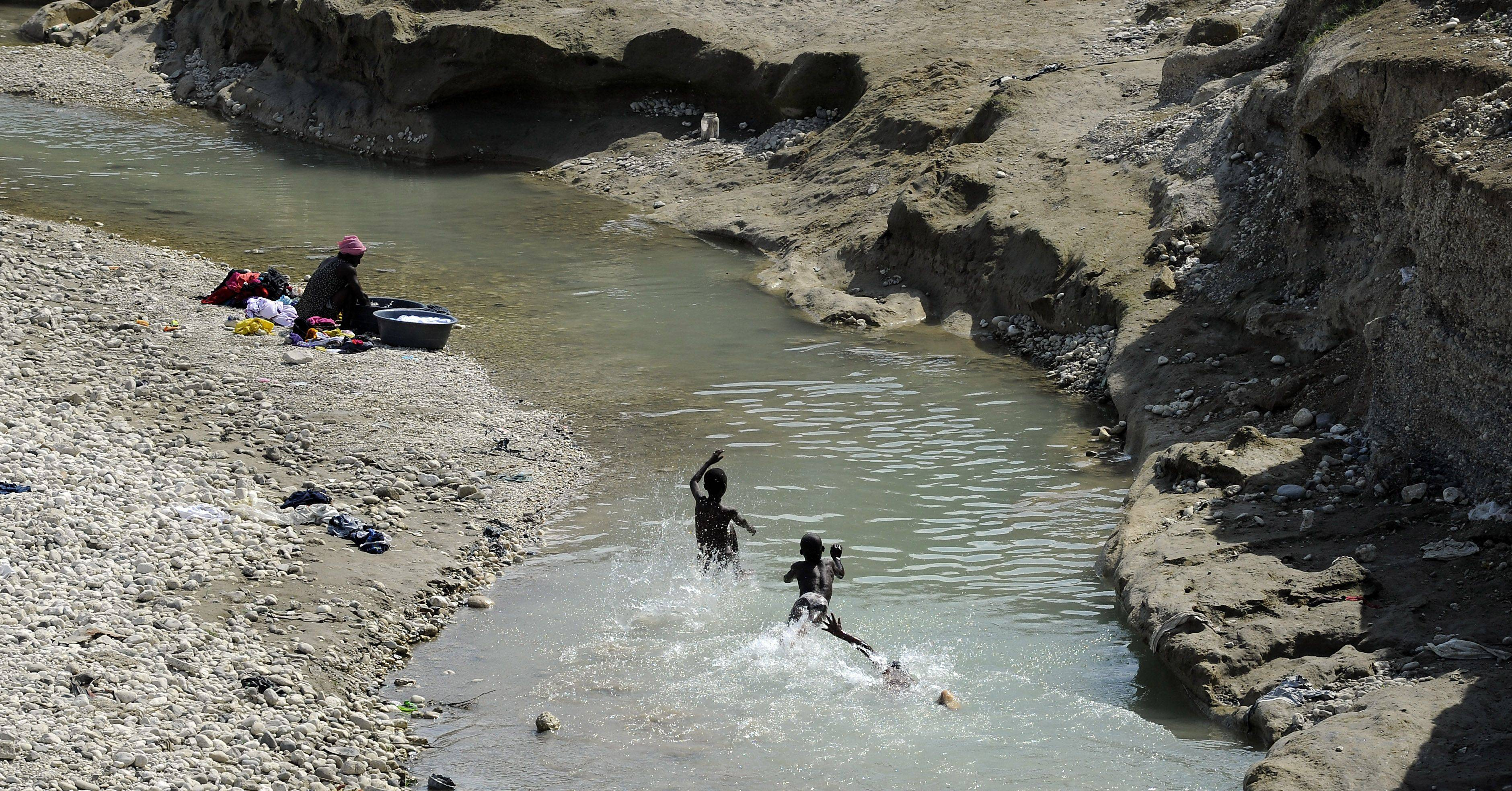 Kids swim in the dirty water while a woman does her laundry near a tent city located near Port-au-Prince.