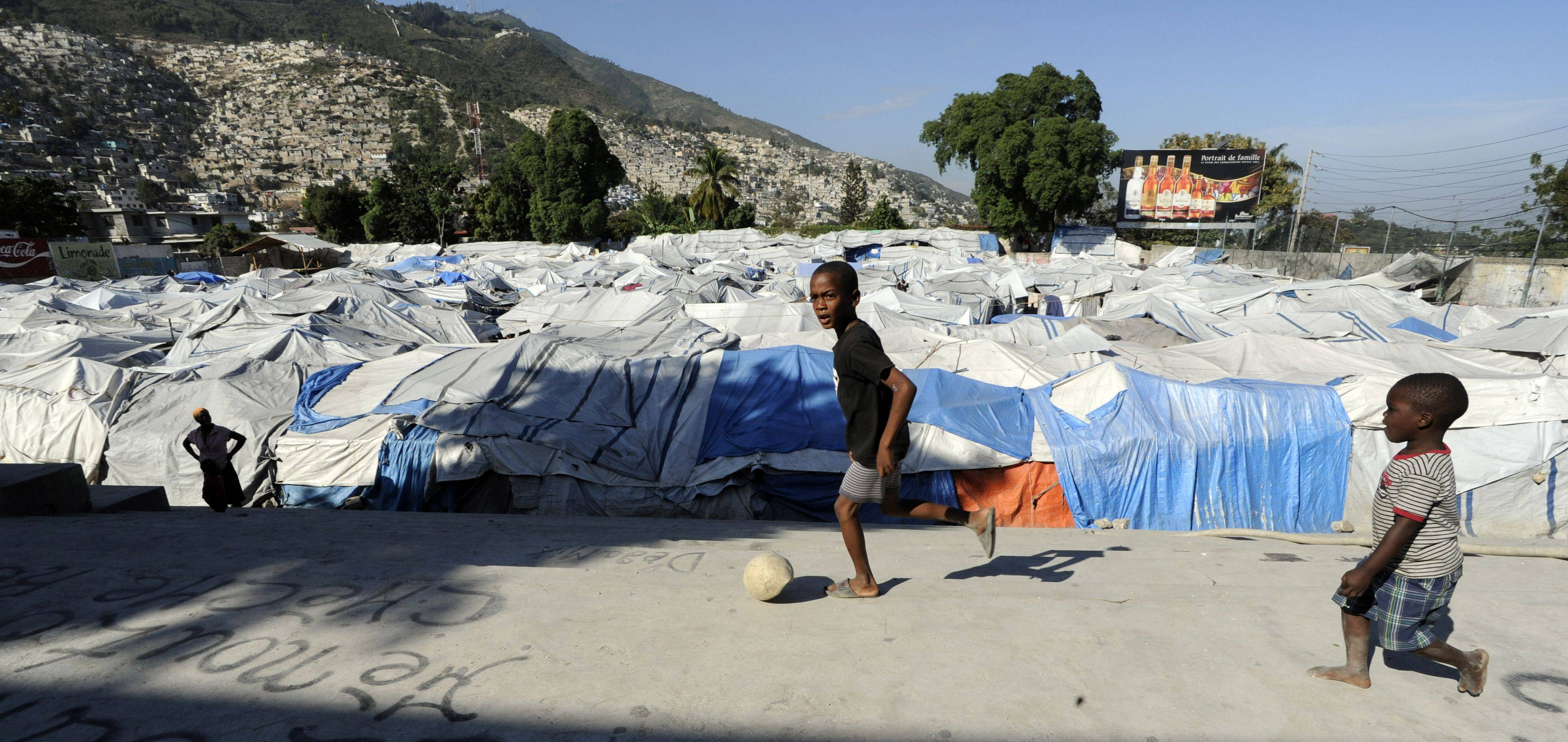 Kids play with a flatten soccer ball in tent city in Port-au-Prince as houses dot the hillside in the background.