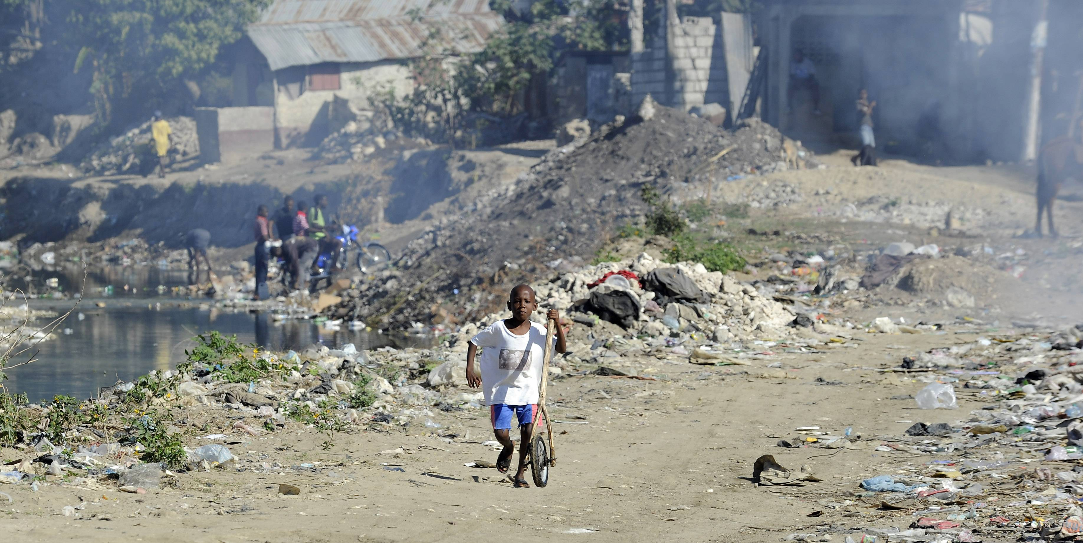 A young Haitian boy plays with a hoop and stick in the trash dump located outside the Jacmel, Haiti.