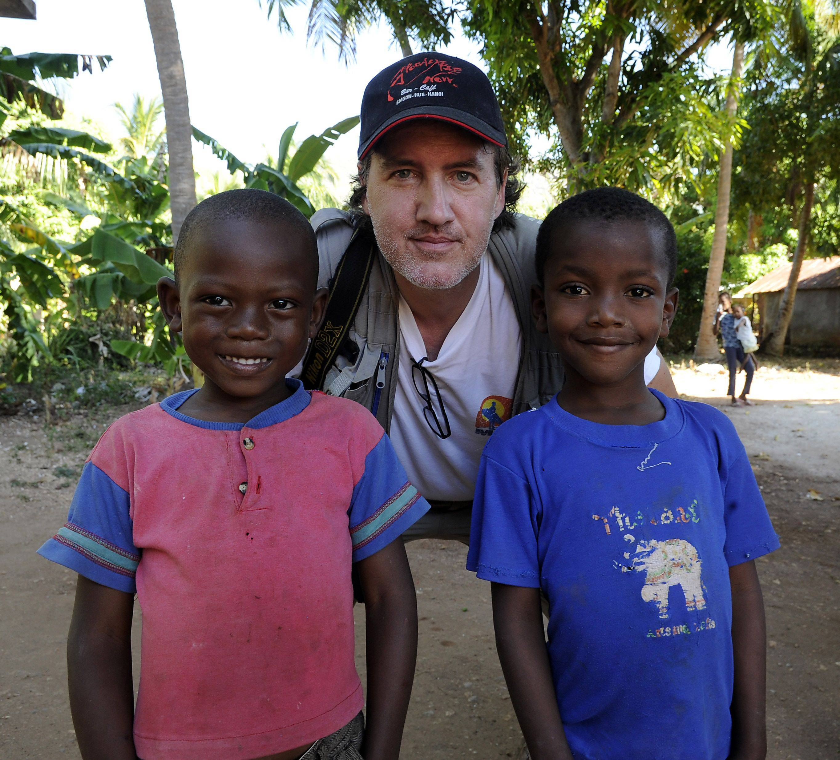 Daily Herald Senior Photographer Mark Welsh poses with Haitian children in Jacmel, Haiti.