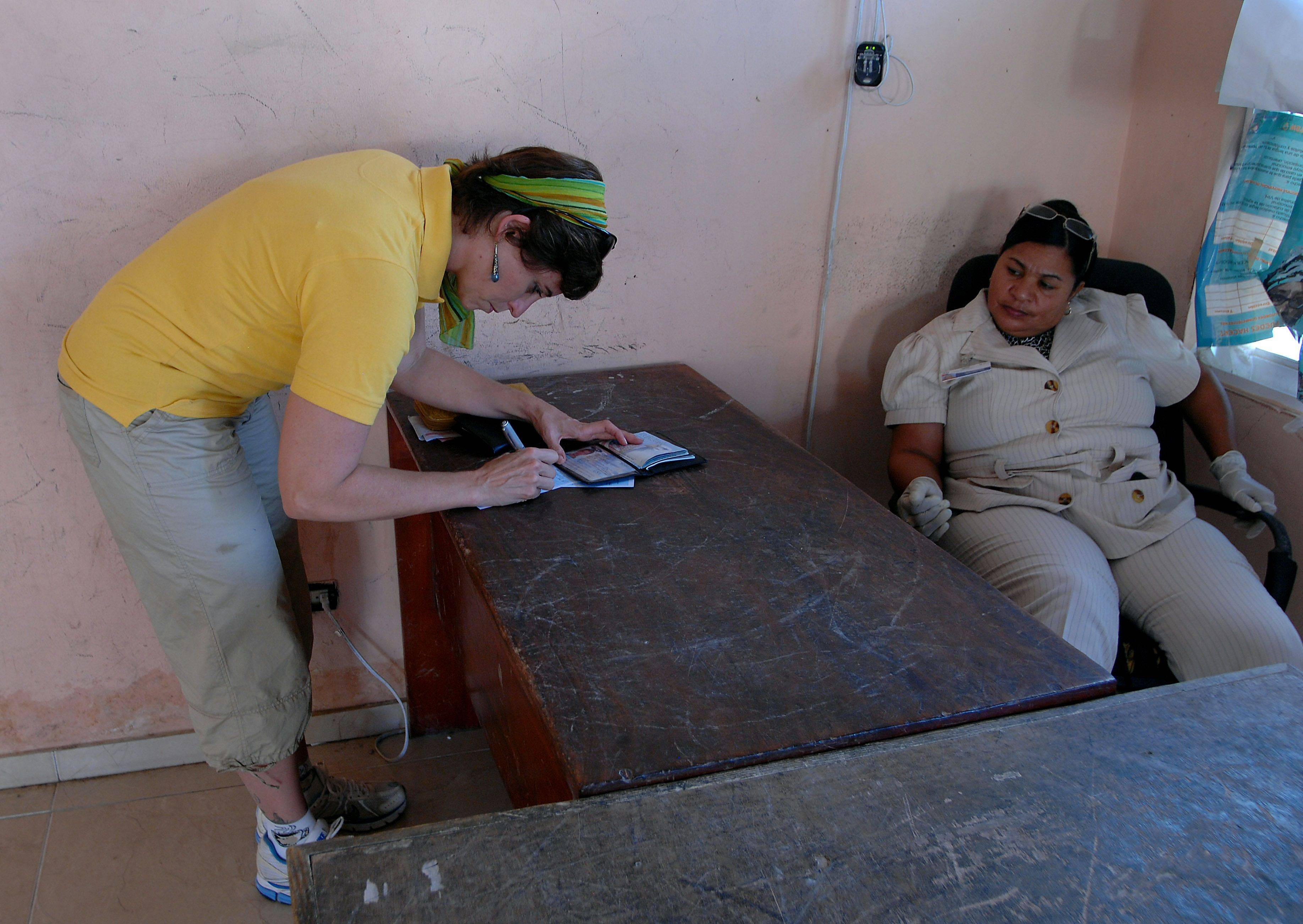 Lisa Ballantine of Elk Grove Village fills out paperwork on the border between Haiti and the Dominican Republic as she heads to her factory that makes water filters in Jacmel, Haiti.