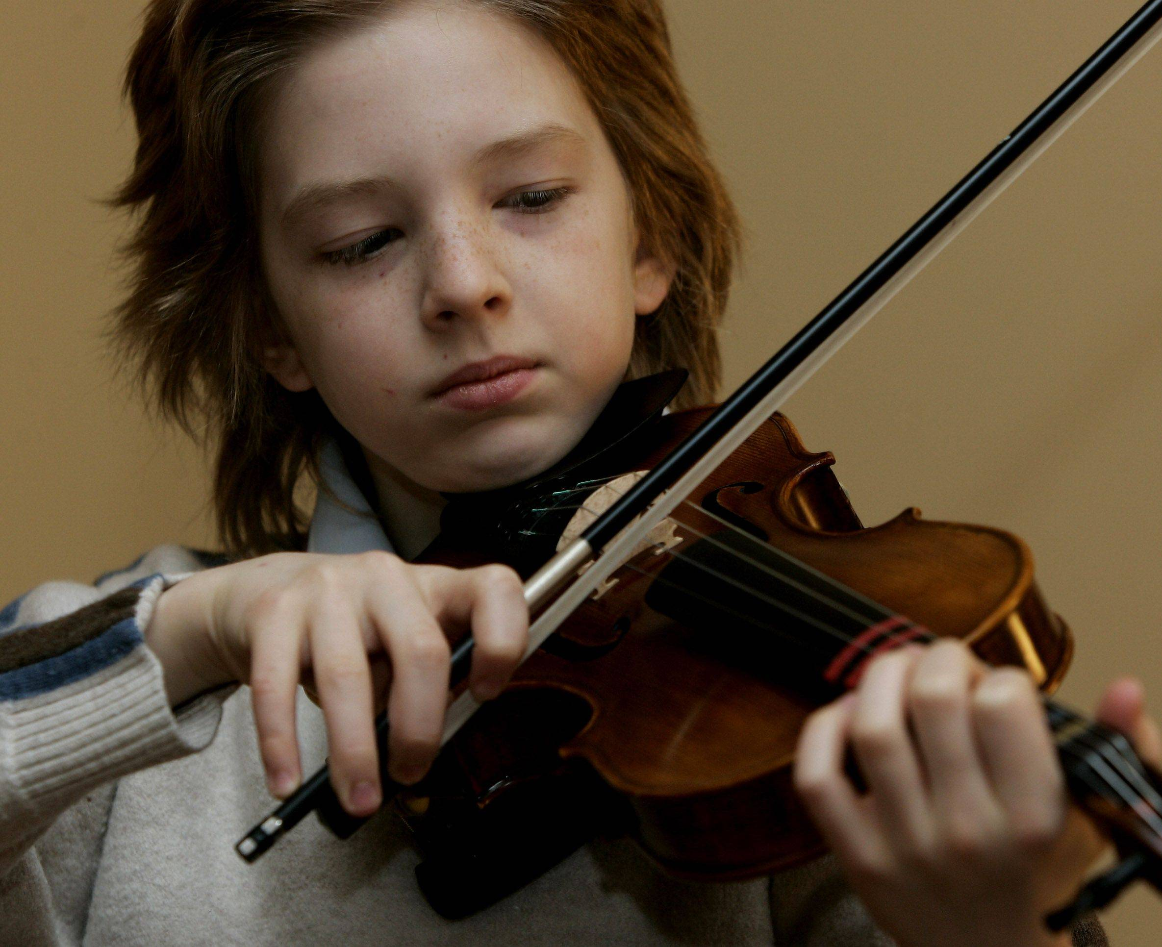 "Gifted student Antony Simonoff practices on the violin at his home in Vernon Hills. Antony recently performed in the Joffrey Ballet production of ""The Nutcracker."""