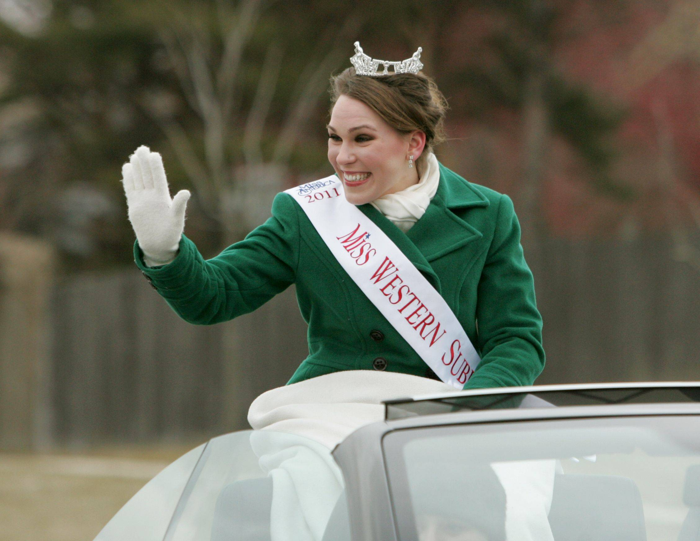 Miss Western Suburbs Samantha Breske of Joliet waves to the crowd during the annual St. Patrick's Day Parade in downtown Naperville.