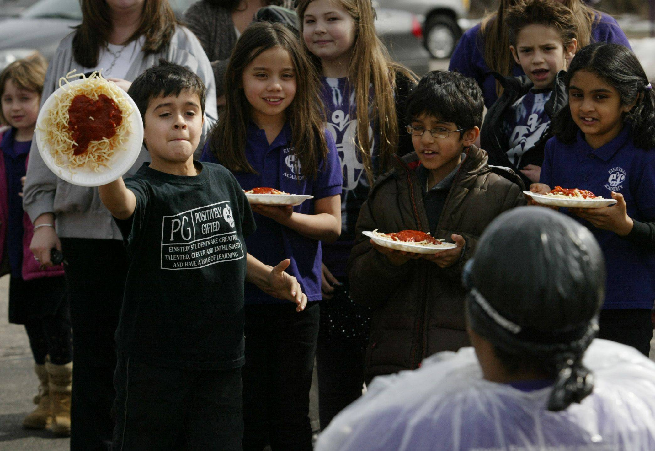 Einstein Academy third grader Brady Iaccino takes the first shot at hitting teacher Jason Smith with a plate full of pasta and marinara sauce Monday in Elgin. The pasta pie tossing was in honor of Pi, a mathematical constant whose value is the ratio of any circle's circumference to its diameter. The number is usually shortened to 3.14, thus the reason for celebrating it on 03/14.