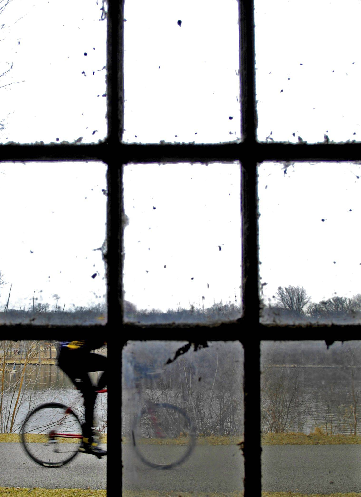 A cyclist is seen speeding past a broken window at the Riverbank Villa Station at Fabyan Forest Preserve in Geneva Tuesday. The building is down the hill from the Fabyan Villa Museum, home to George and Nelle Fabyan from 1905 thru 1939.